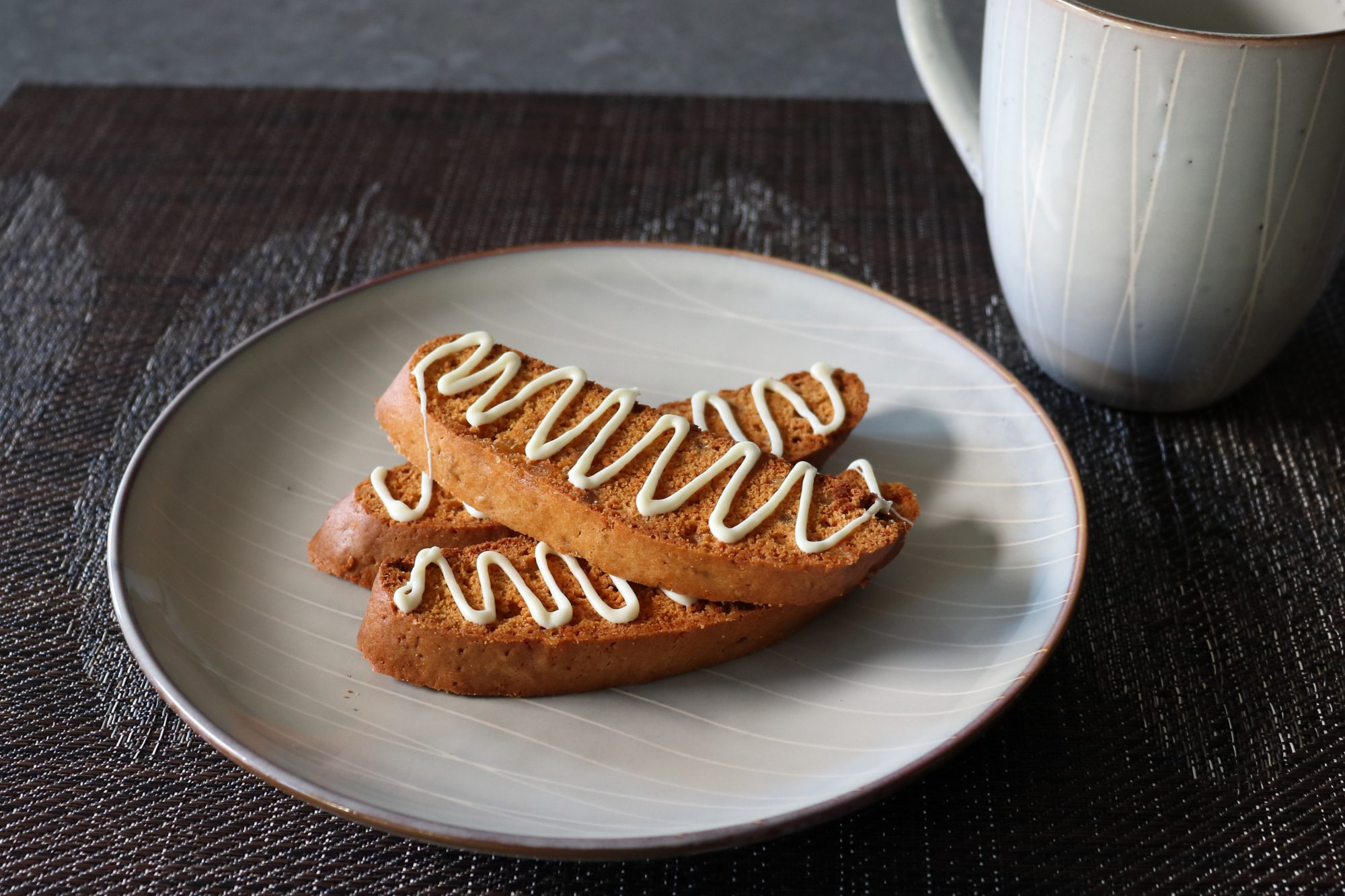 Three pale brown biscotti drizzled with white chocolate arranged on a plate