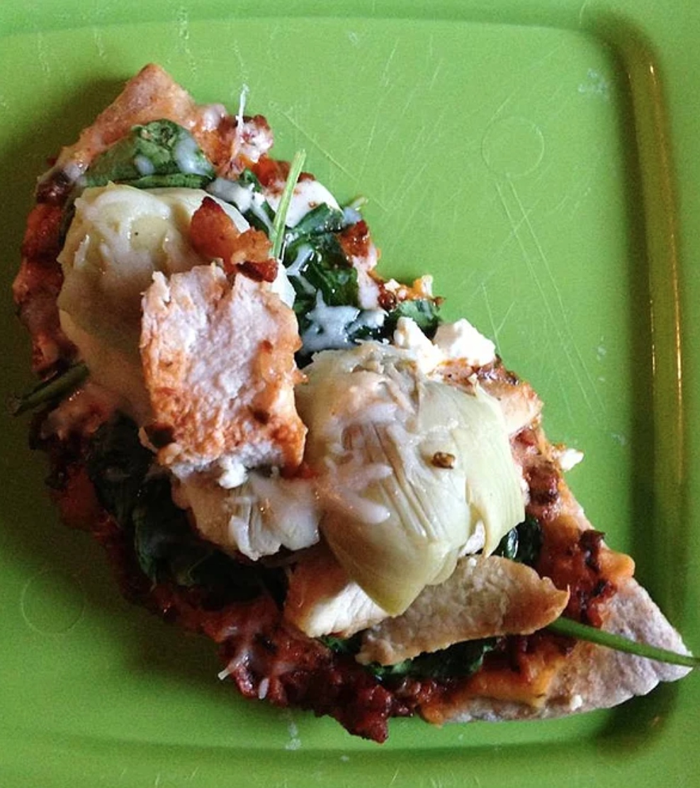 This creative pita pizza is topped with jarred Alfredo sauce, hummus, basil pesto, spinach, artichoke hearts, frozen chicken tenders, and three kinds of cheese.