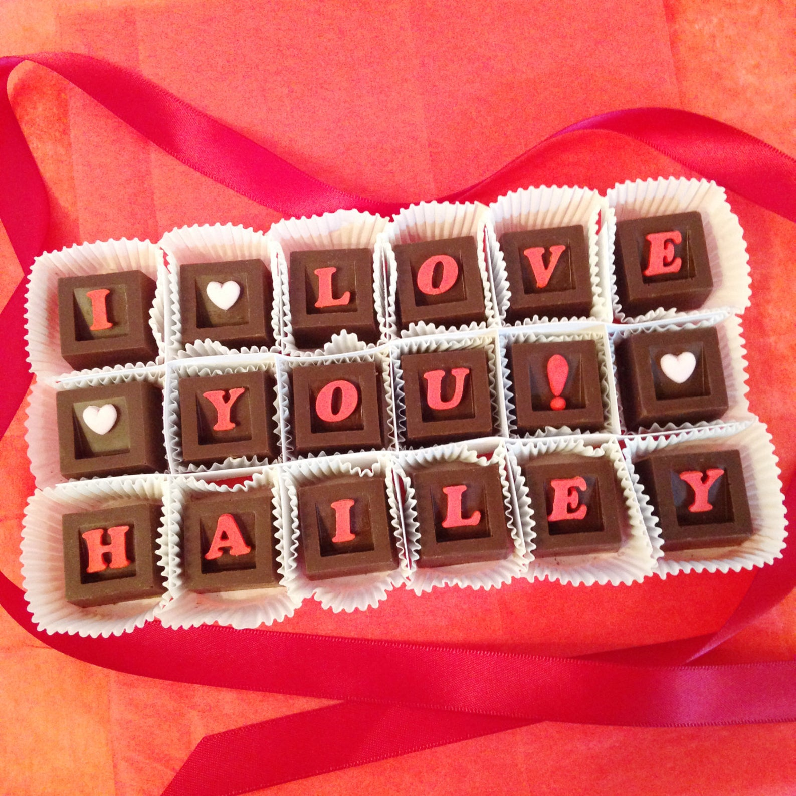 "personalized chocolates that read ""I love you Hailey"" with one letter on each piece of chocolate"