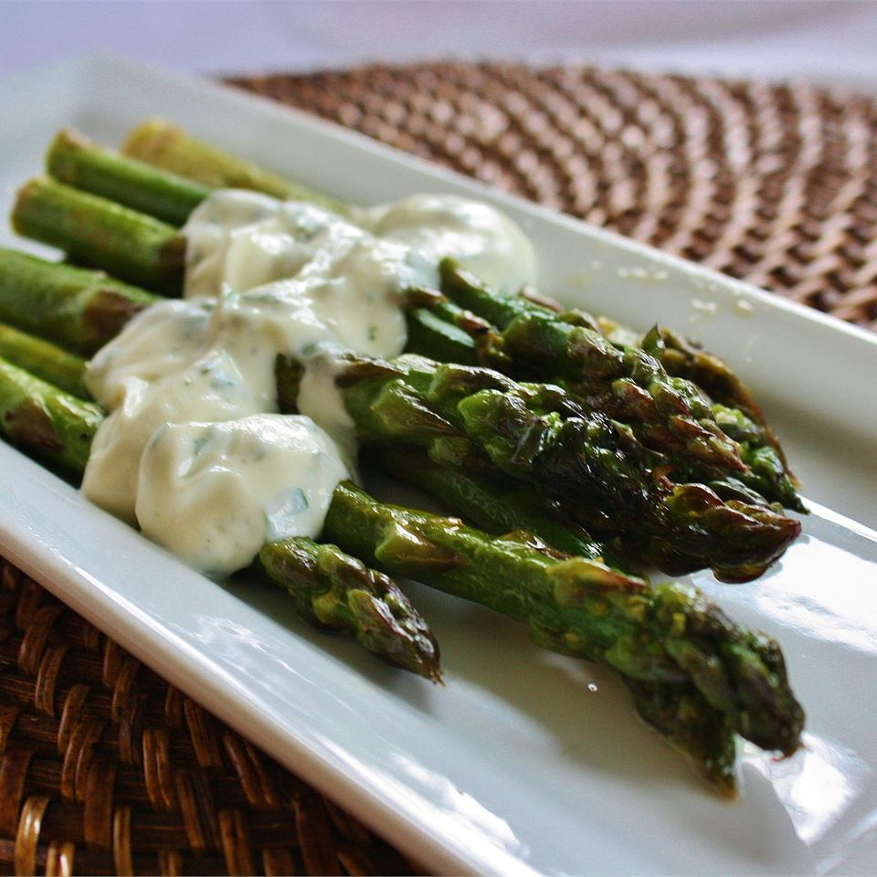 grilled asparagus with cilantro butter on white plate