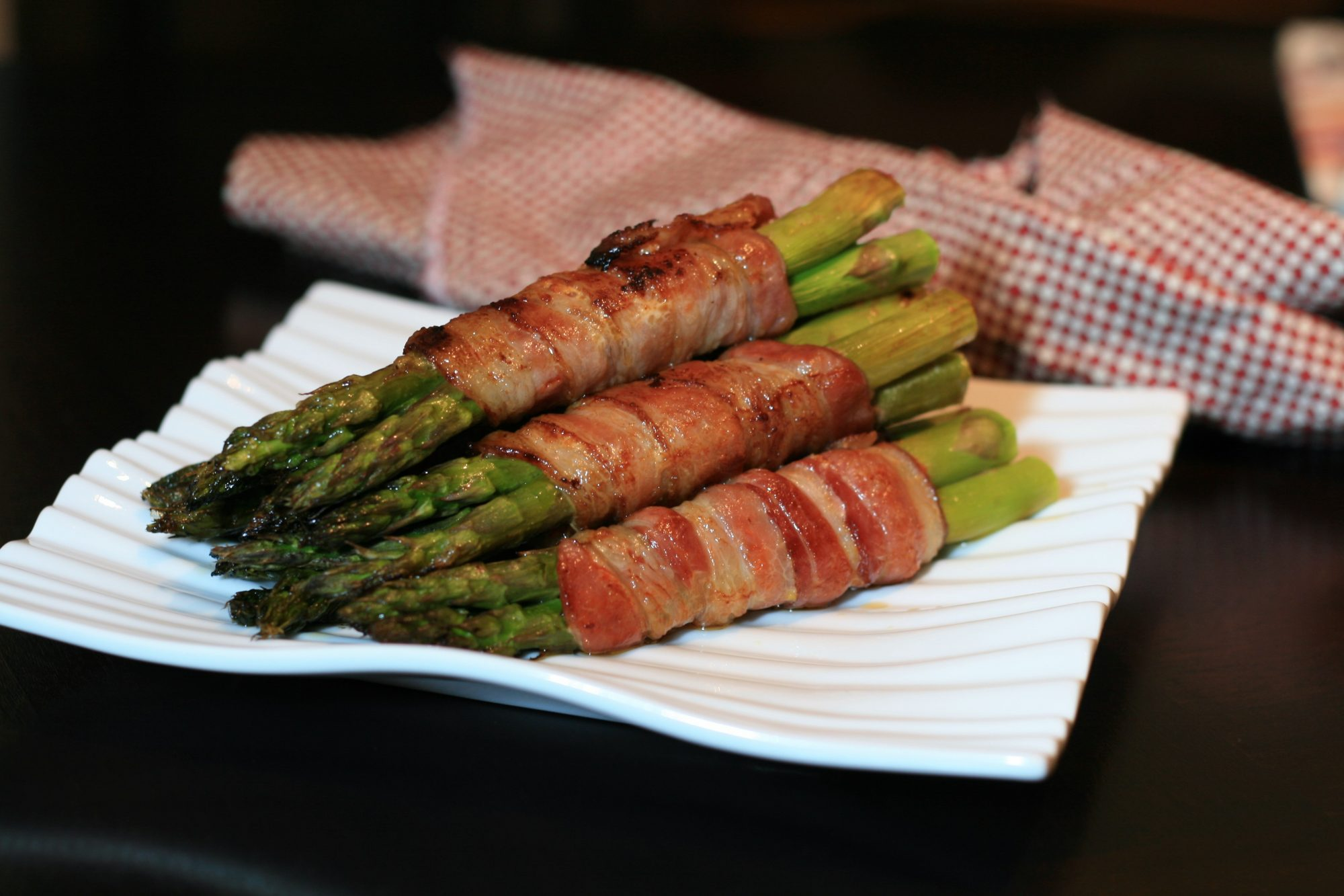 asparagus wrapped in bacon on white plate