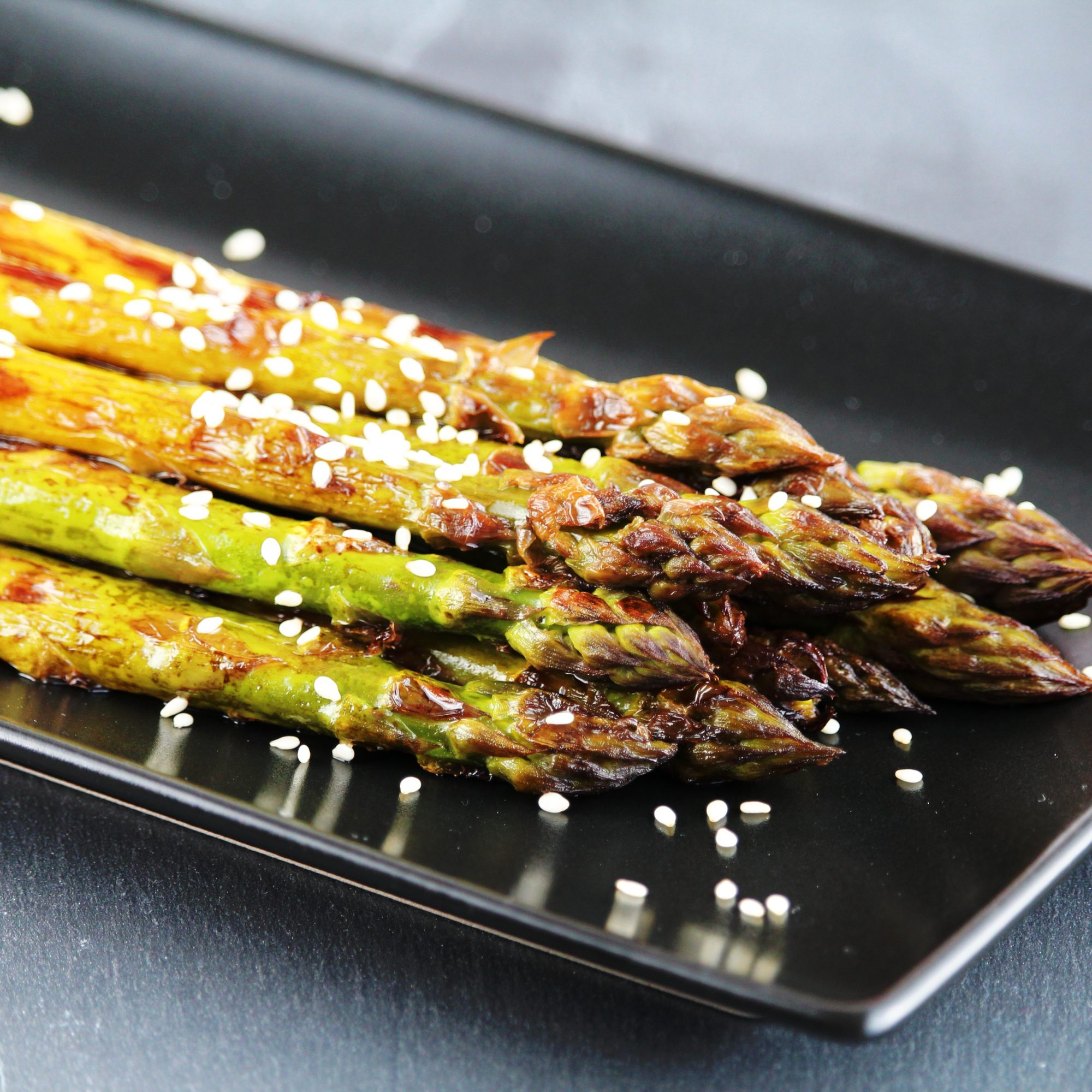 grilled asparagus with sesame seeds on black plate