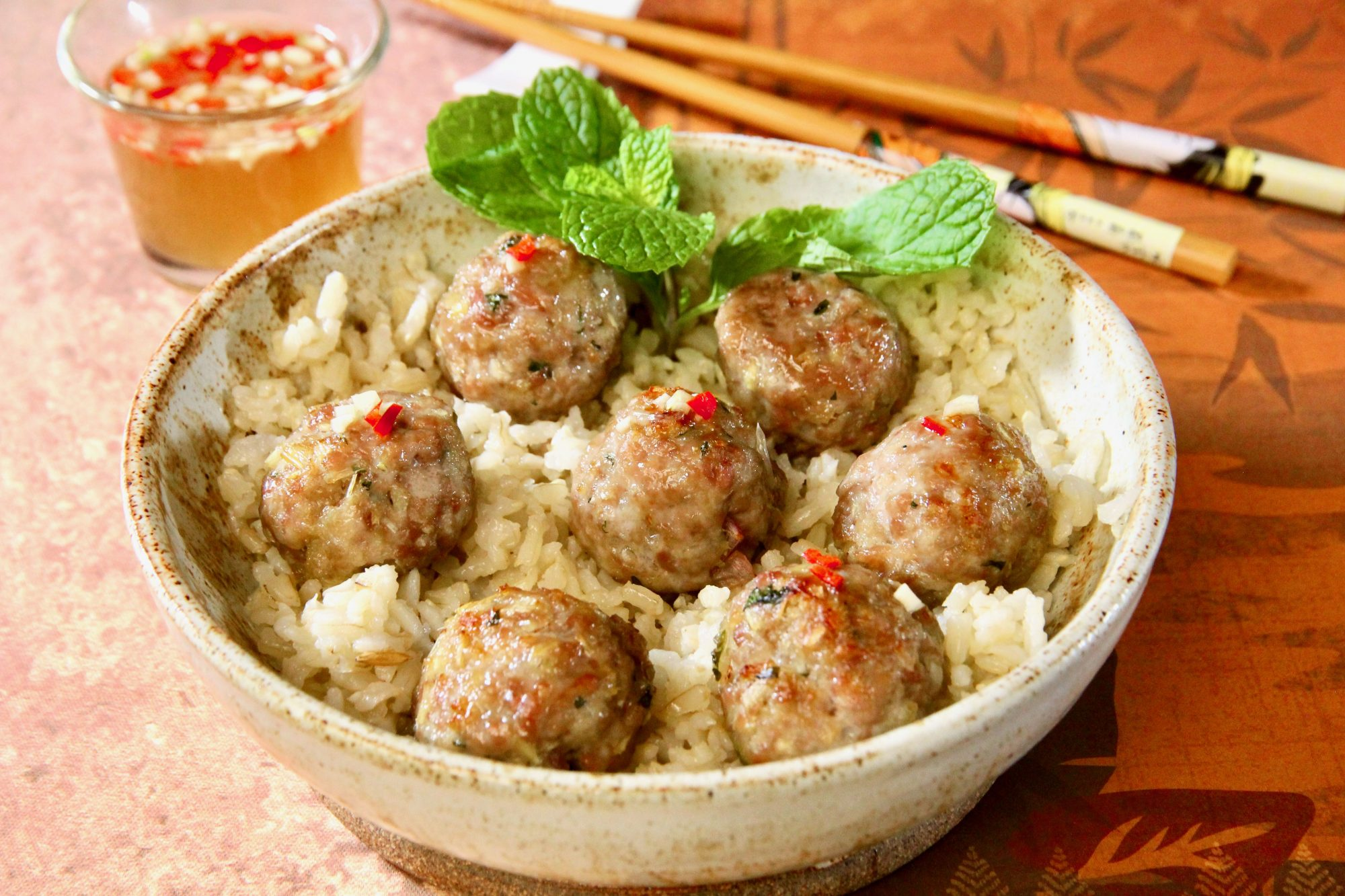 a bowl of baked pork meatballs arranged over rice, garnished with fresh mint