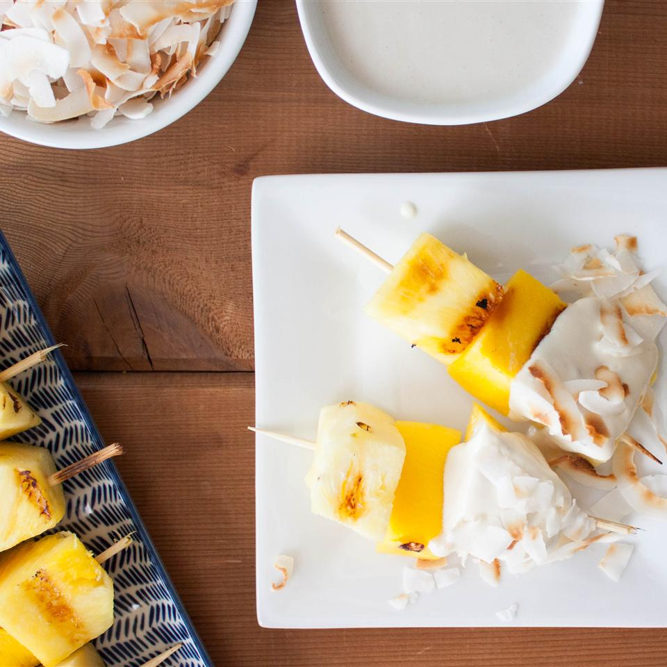 pineapple and coconut skewers with coconut dip topping on white plate