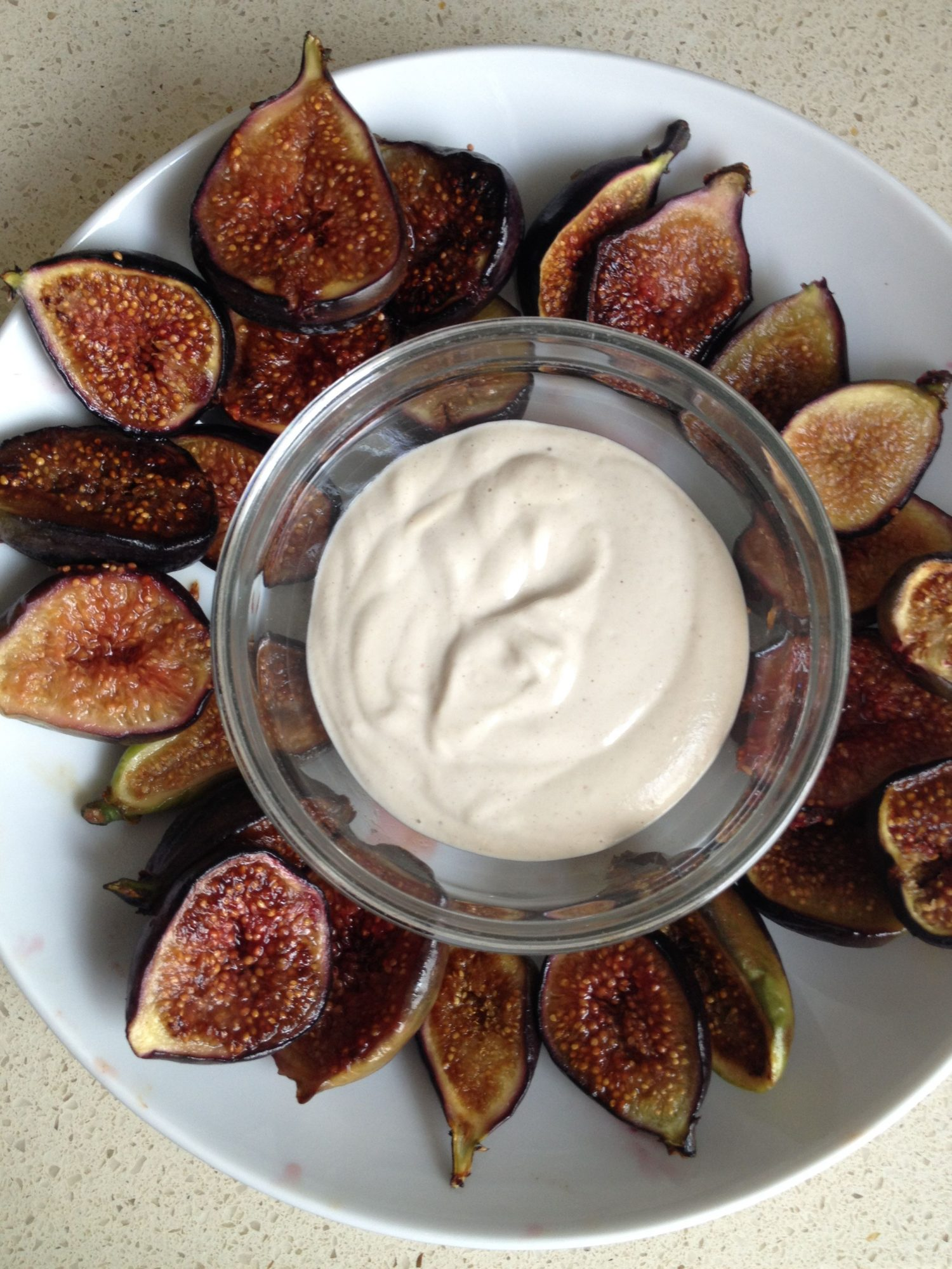 sauteed fig halves on white plate with cashew cream sauce