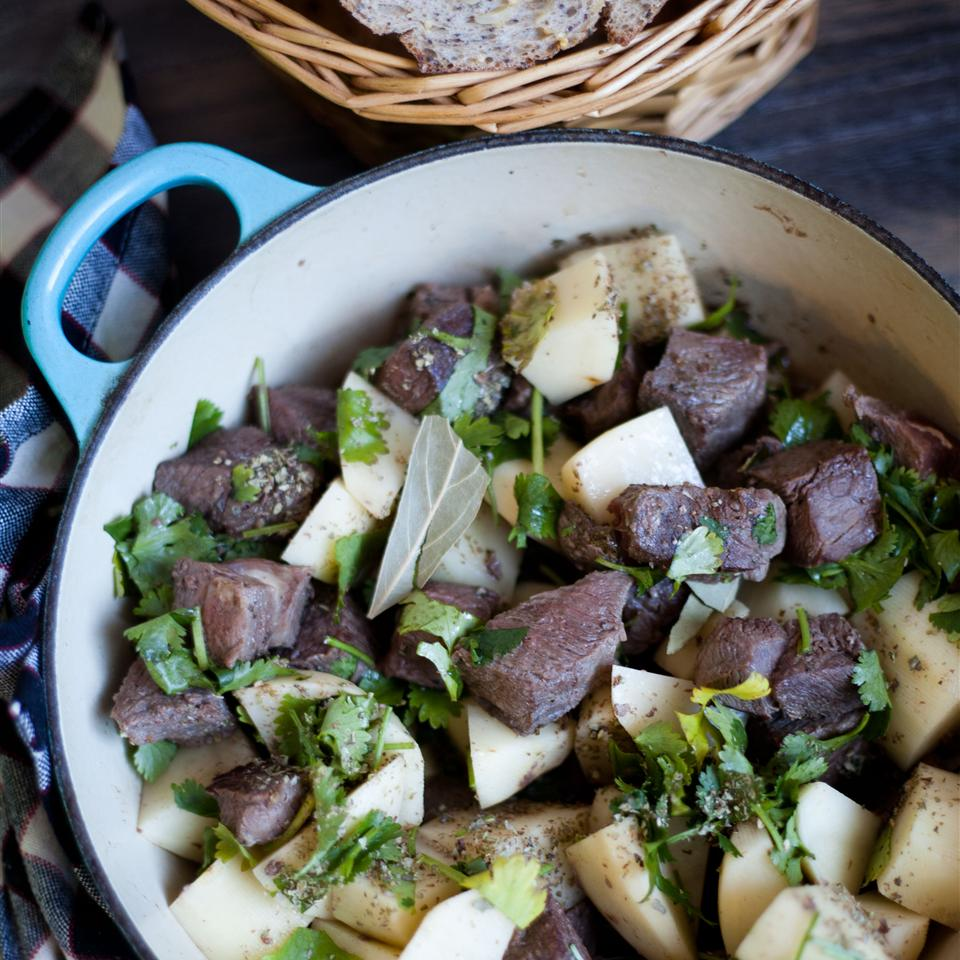 lamb stew with potatoes and cilantro in dutch oven