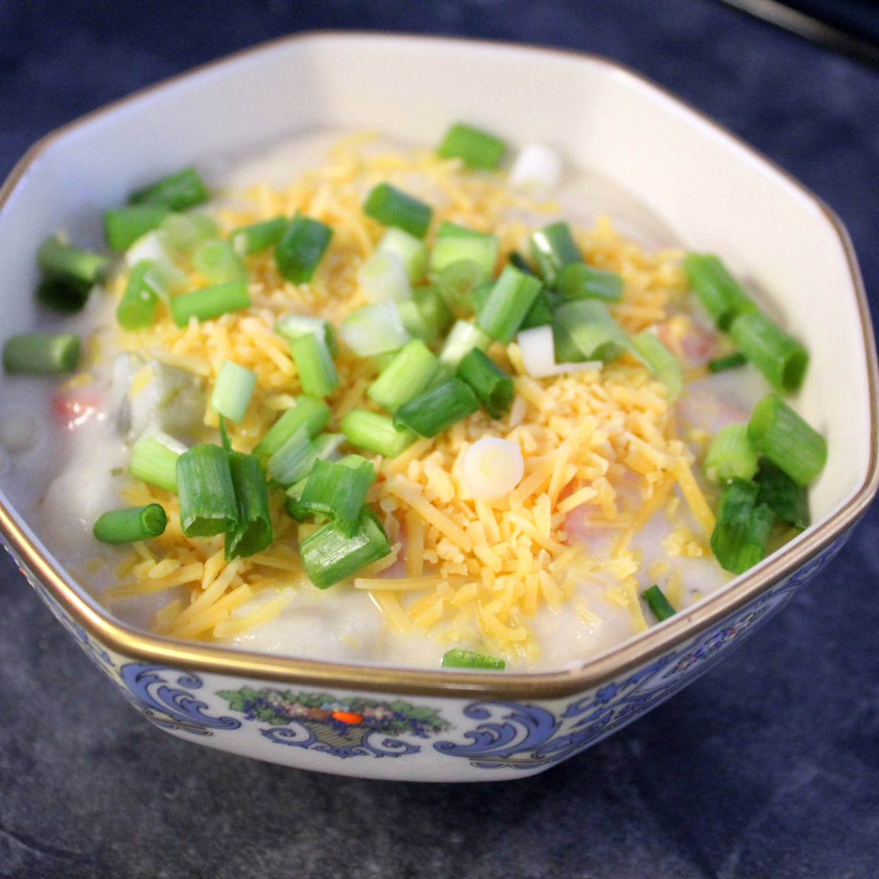 bowl of potato soup with cheese and green onions on top