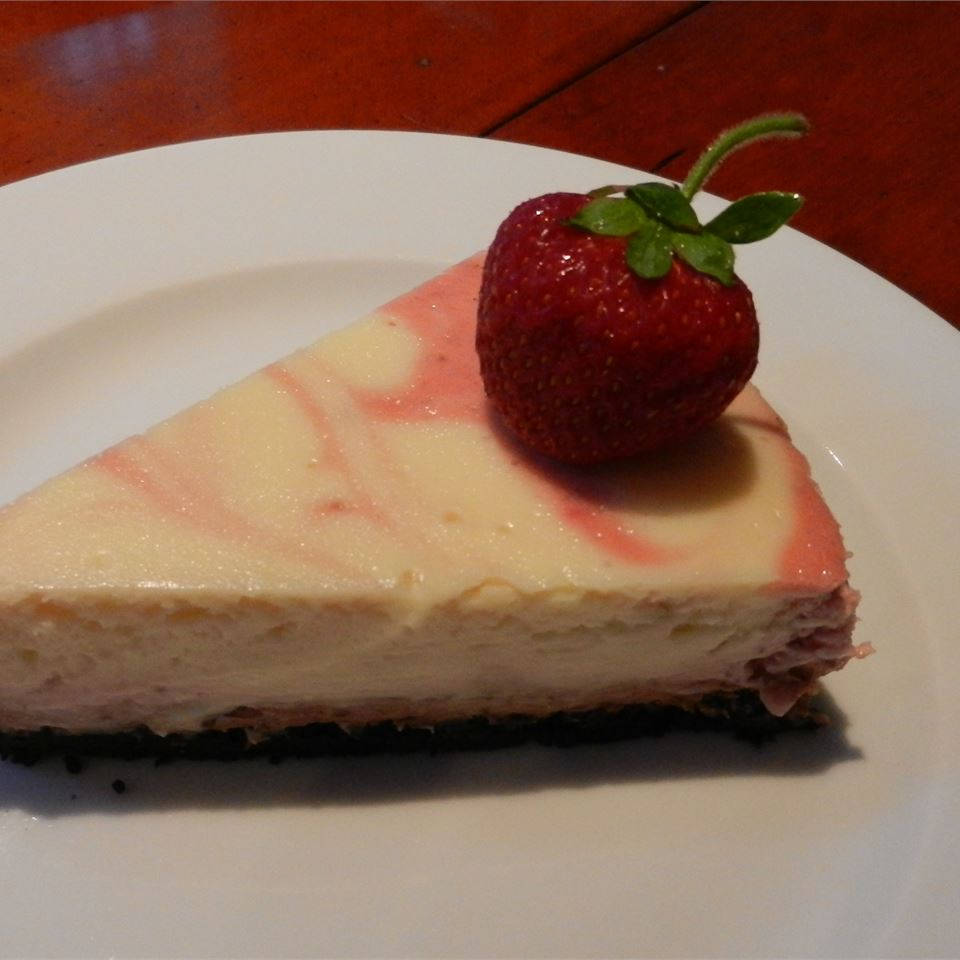 cheesecake with strawberry swirl and chocolate crust with strawberry on top