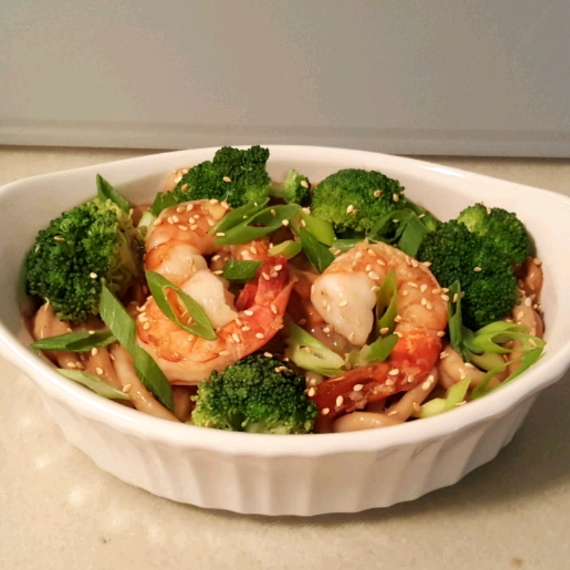 peanut butter noodles with shrimp and broccoli in a white dish
