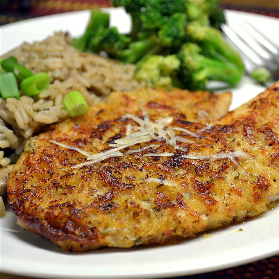 crusted tilapia with rice pilaf and broccoli on a white plate