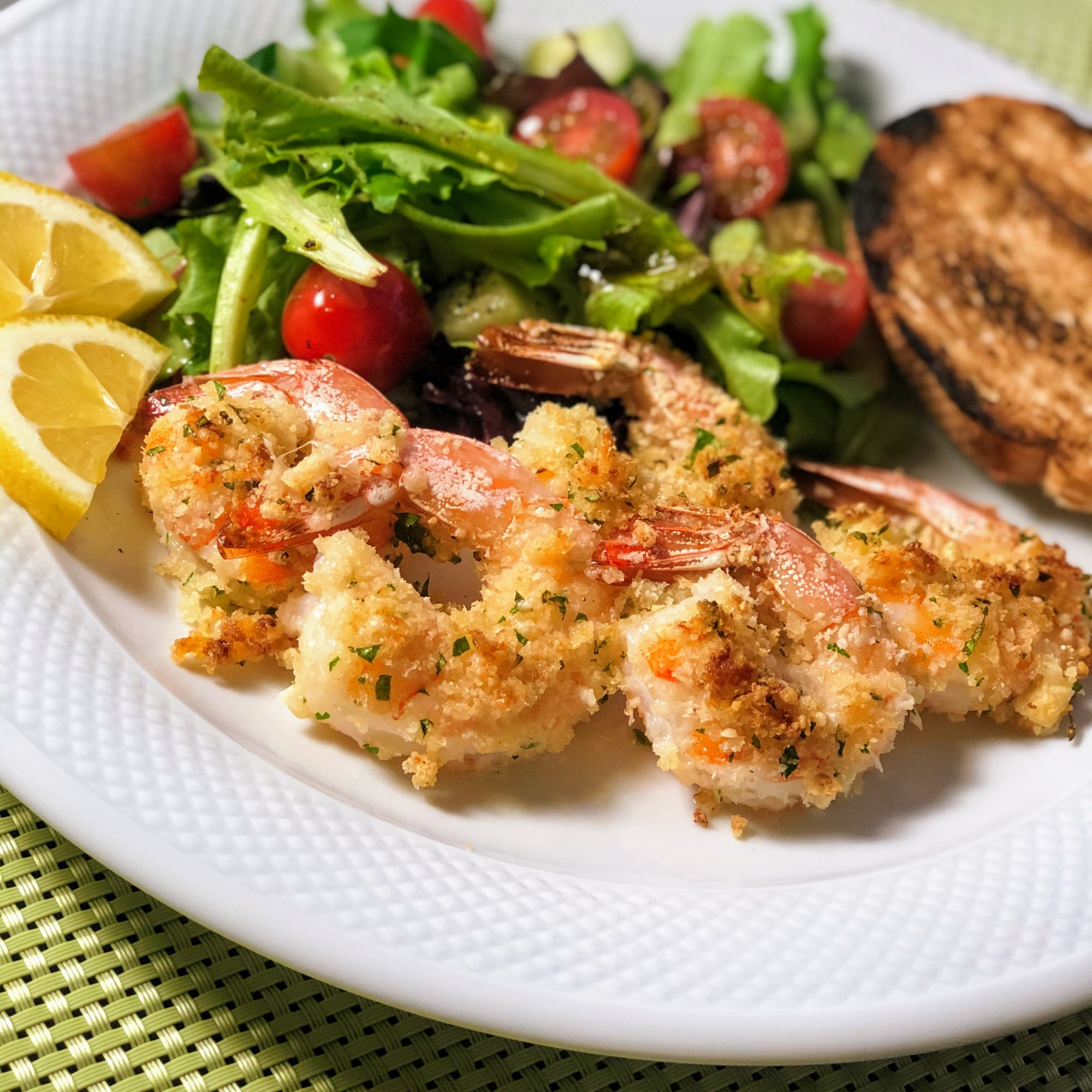 Garlic Parmesan Shrimp with a salad on a white plate