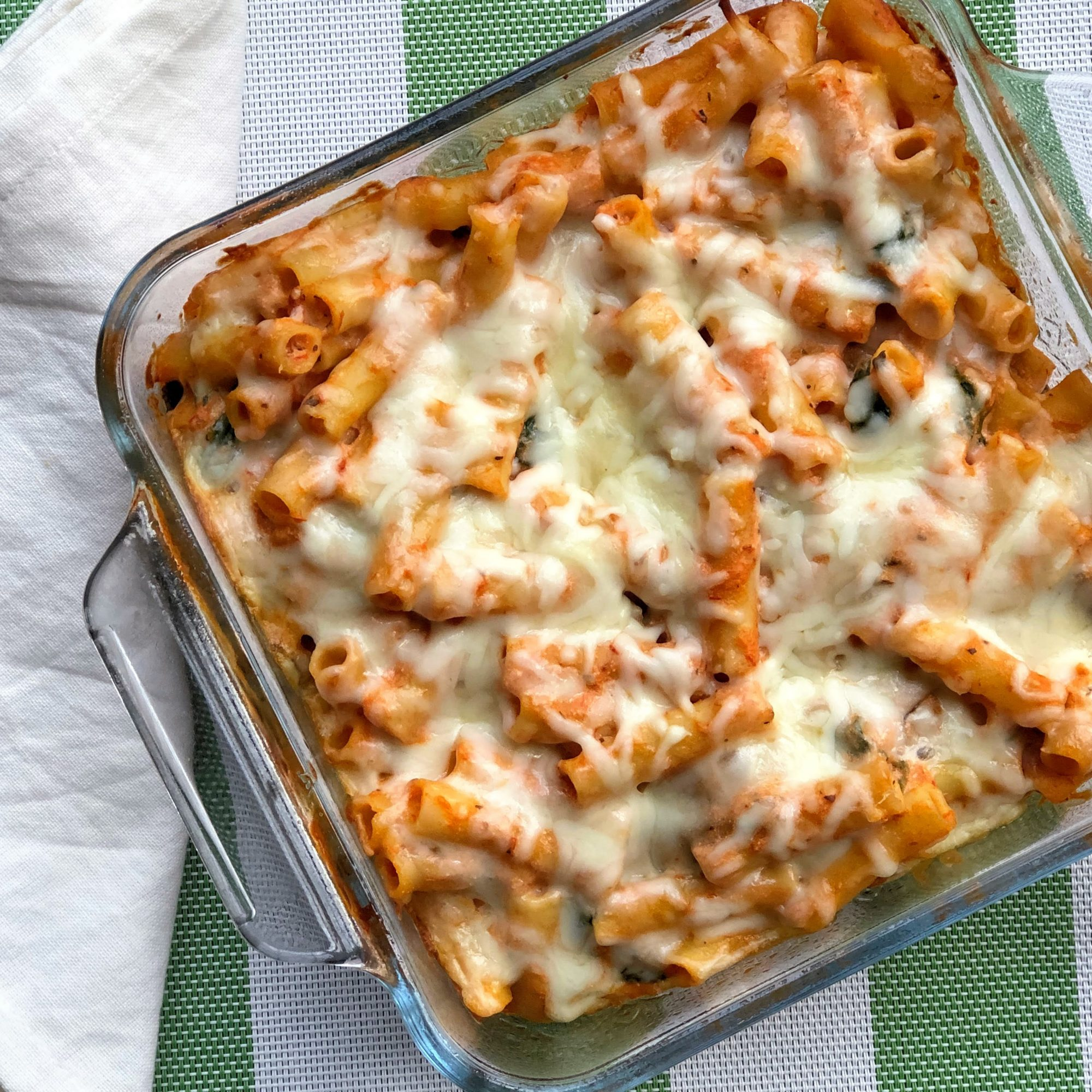 baked ziti in red sauce with cheese in a glass dish
