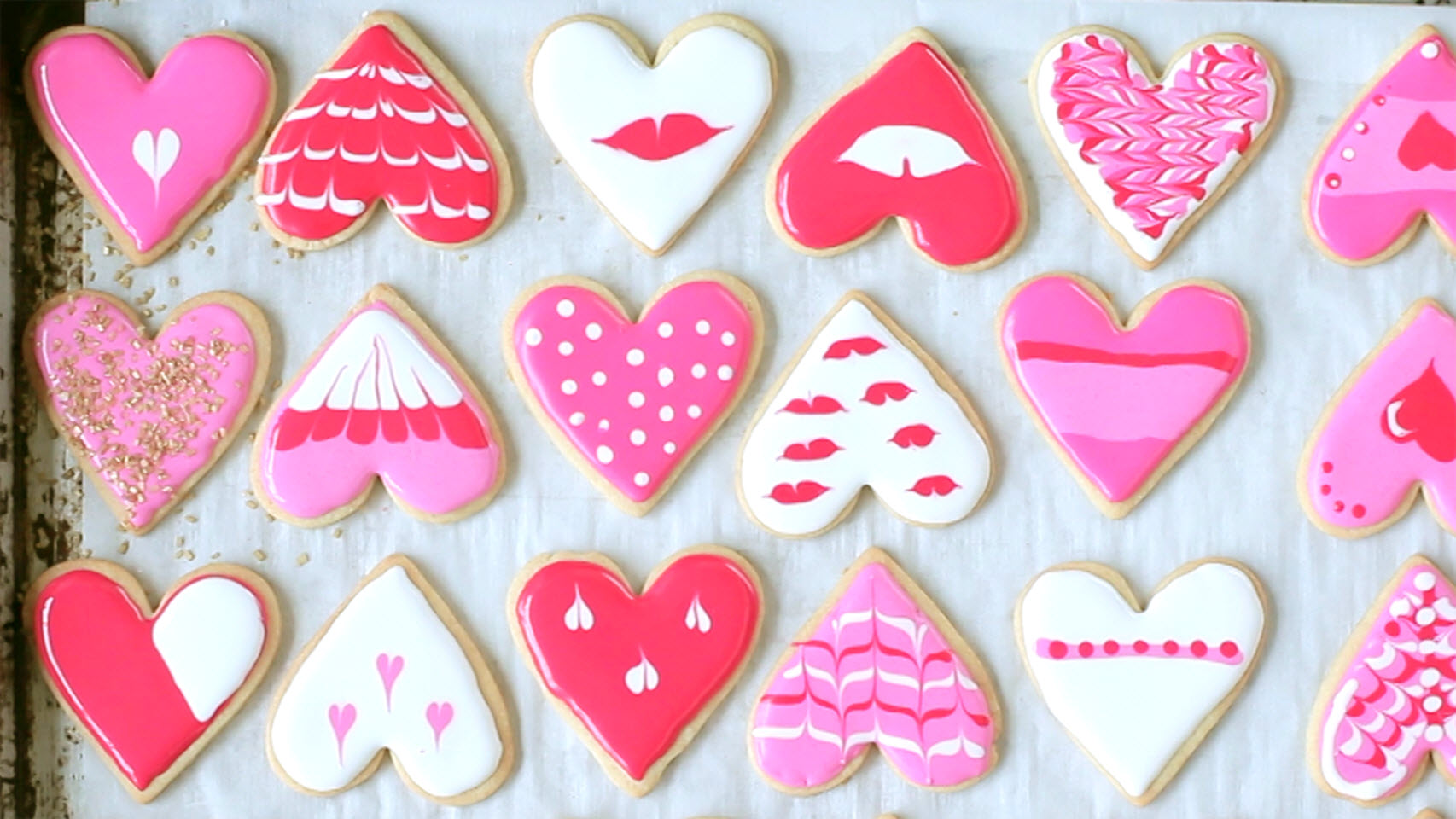 overhead view of heart shaped cookies decorated with red, pink, and white royal icing for valentine's day