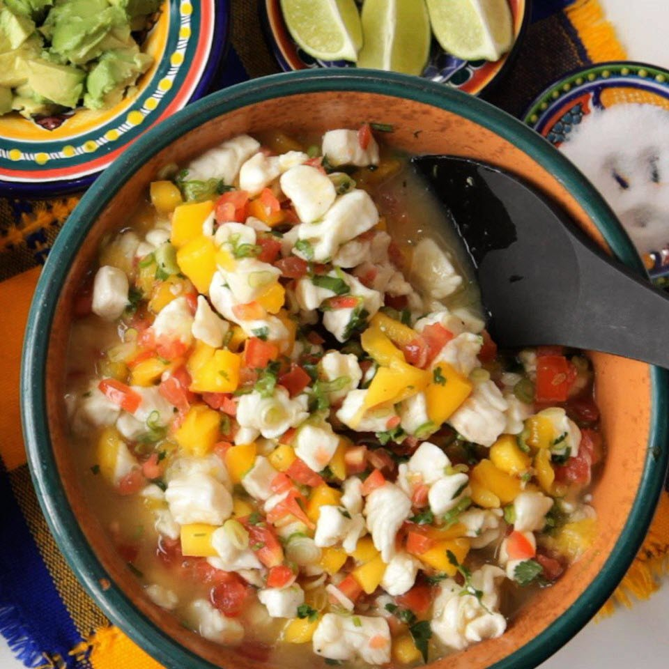 ceviche with white fish, mango, tomatoes, and cilantro in bowl with serving spoon