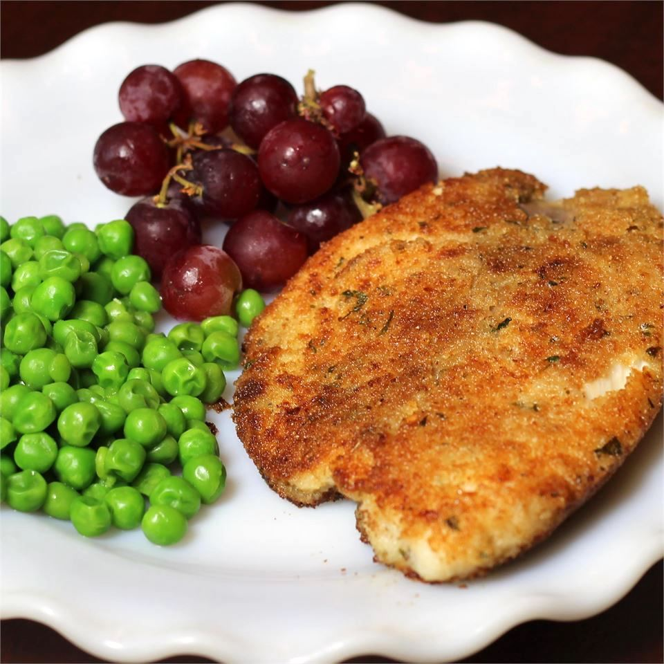 breaded fish with peas and grapes on the side