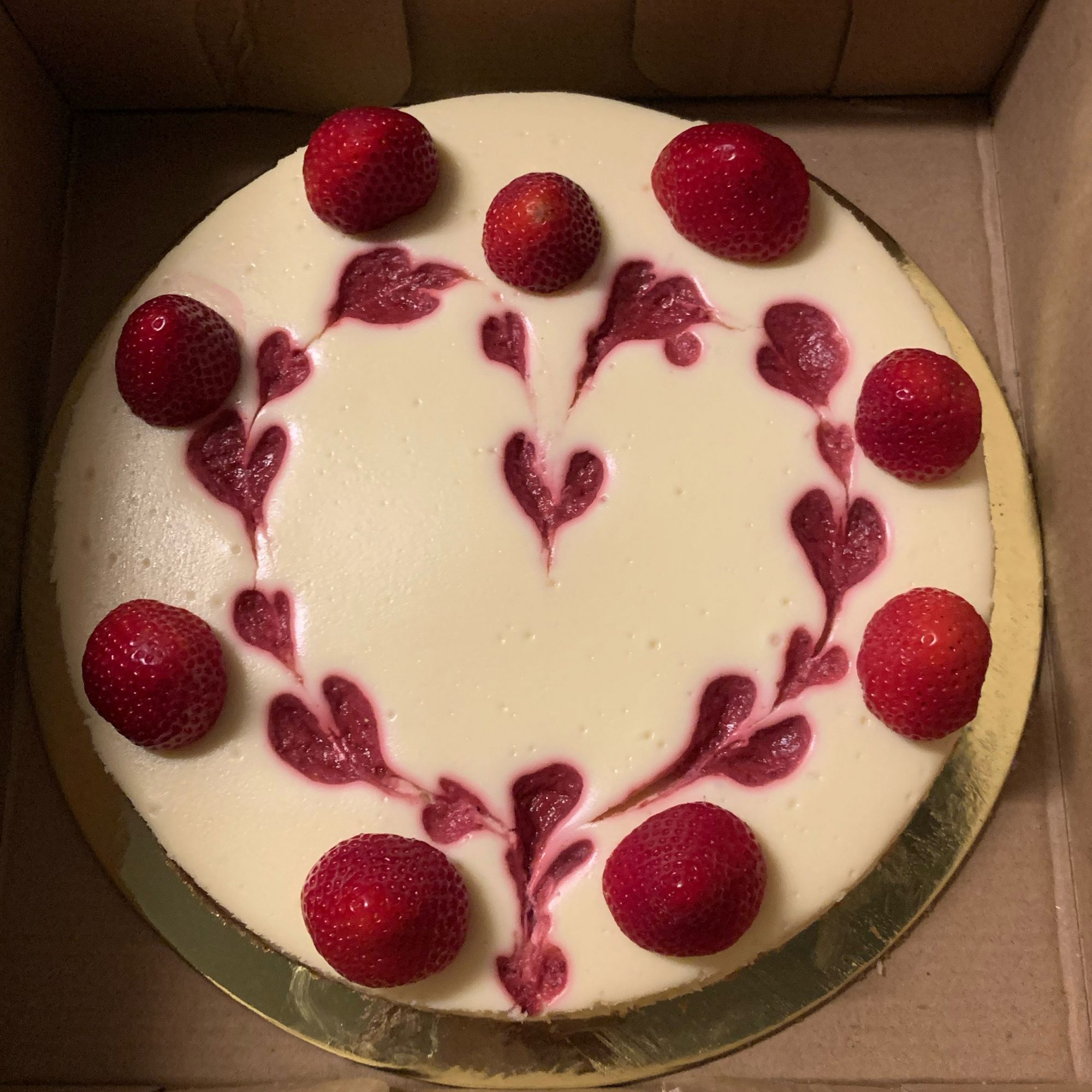 whole cheesecake with strawberry heart decoration