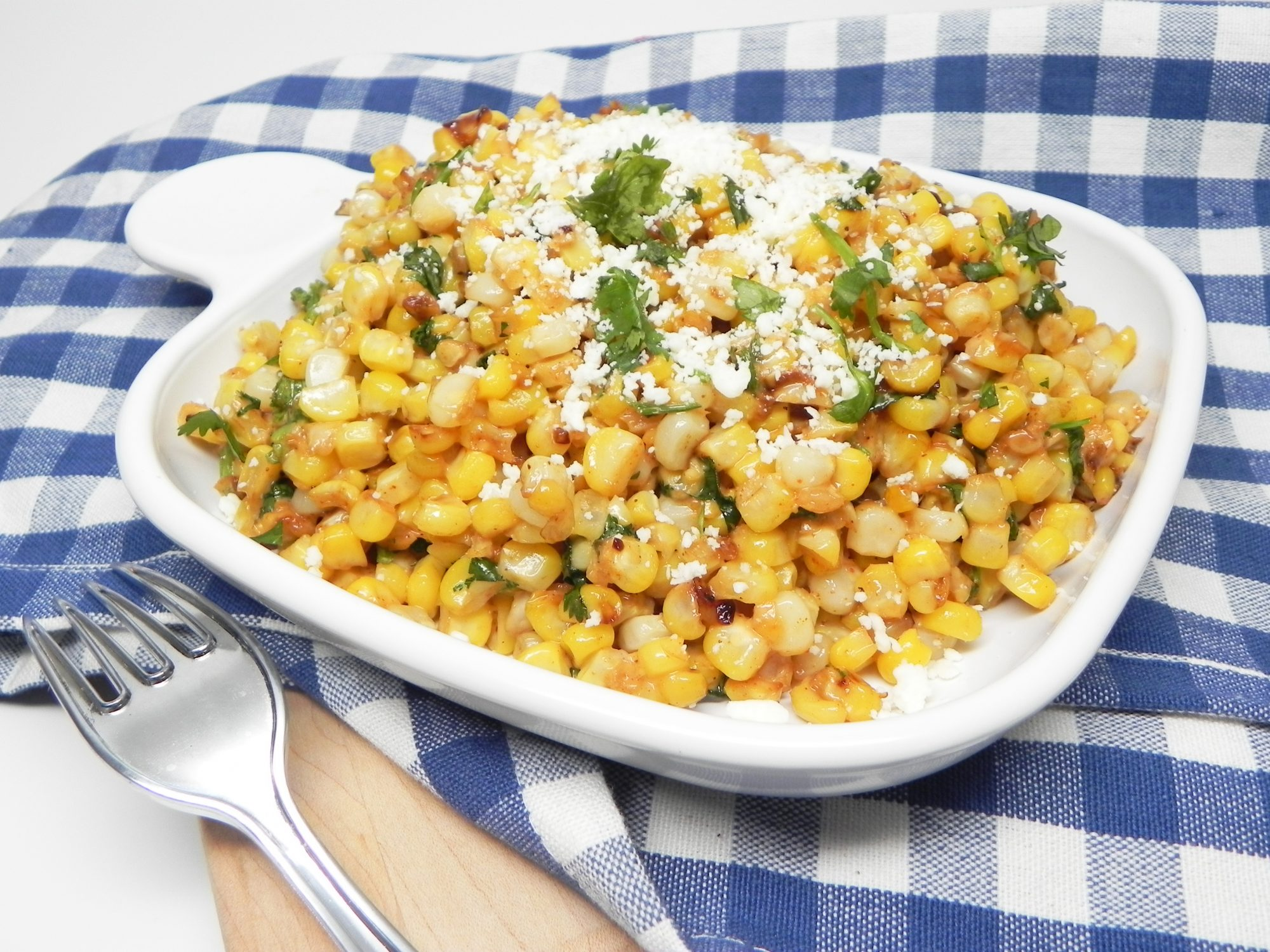 grilled corn with cheese and cilantro on white plate