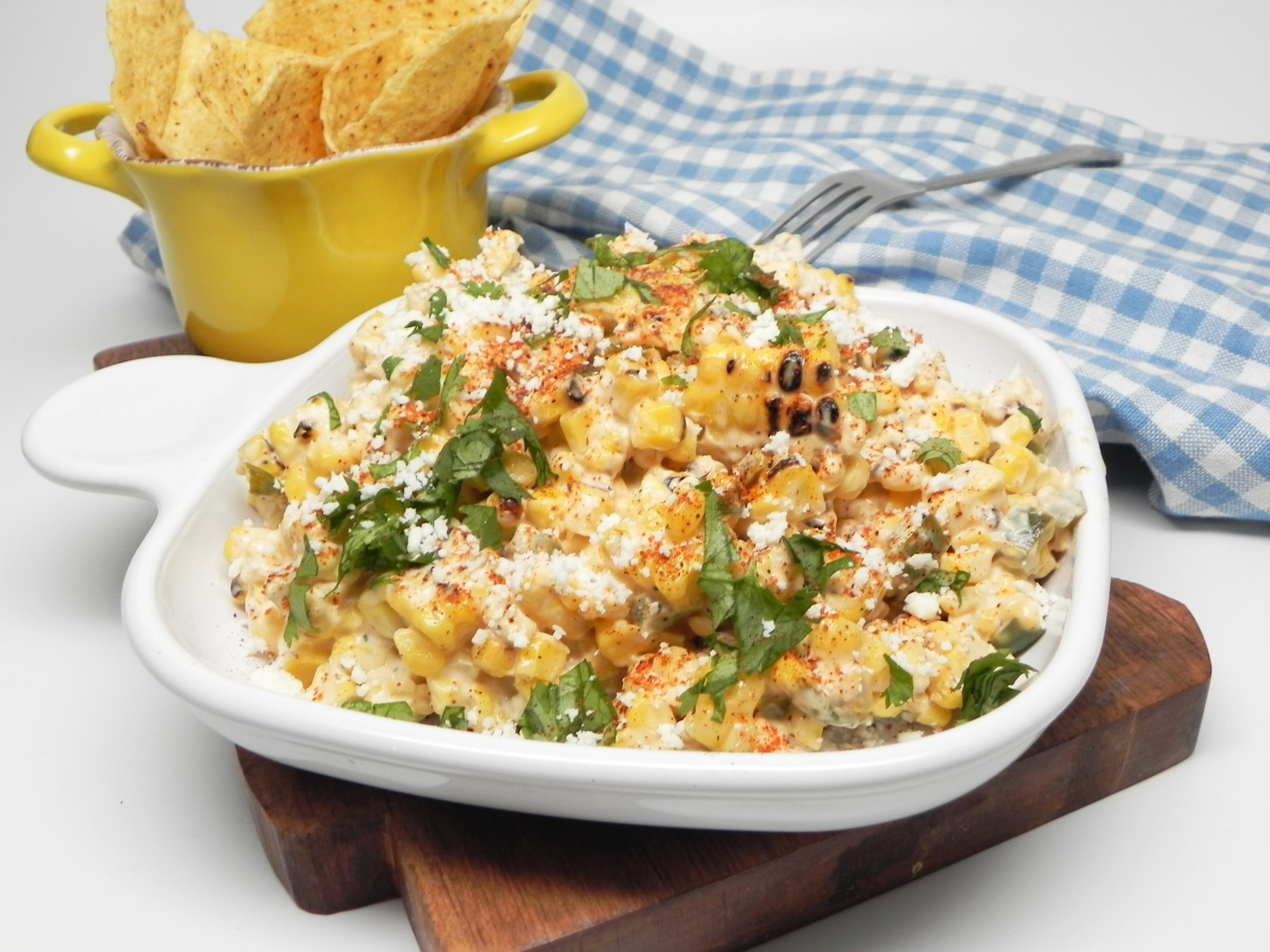 creamy grillec ron dip with cheese, spices, and cilantro in bowl next to chips