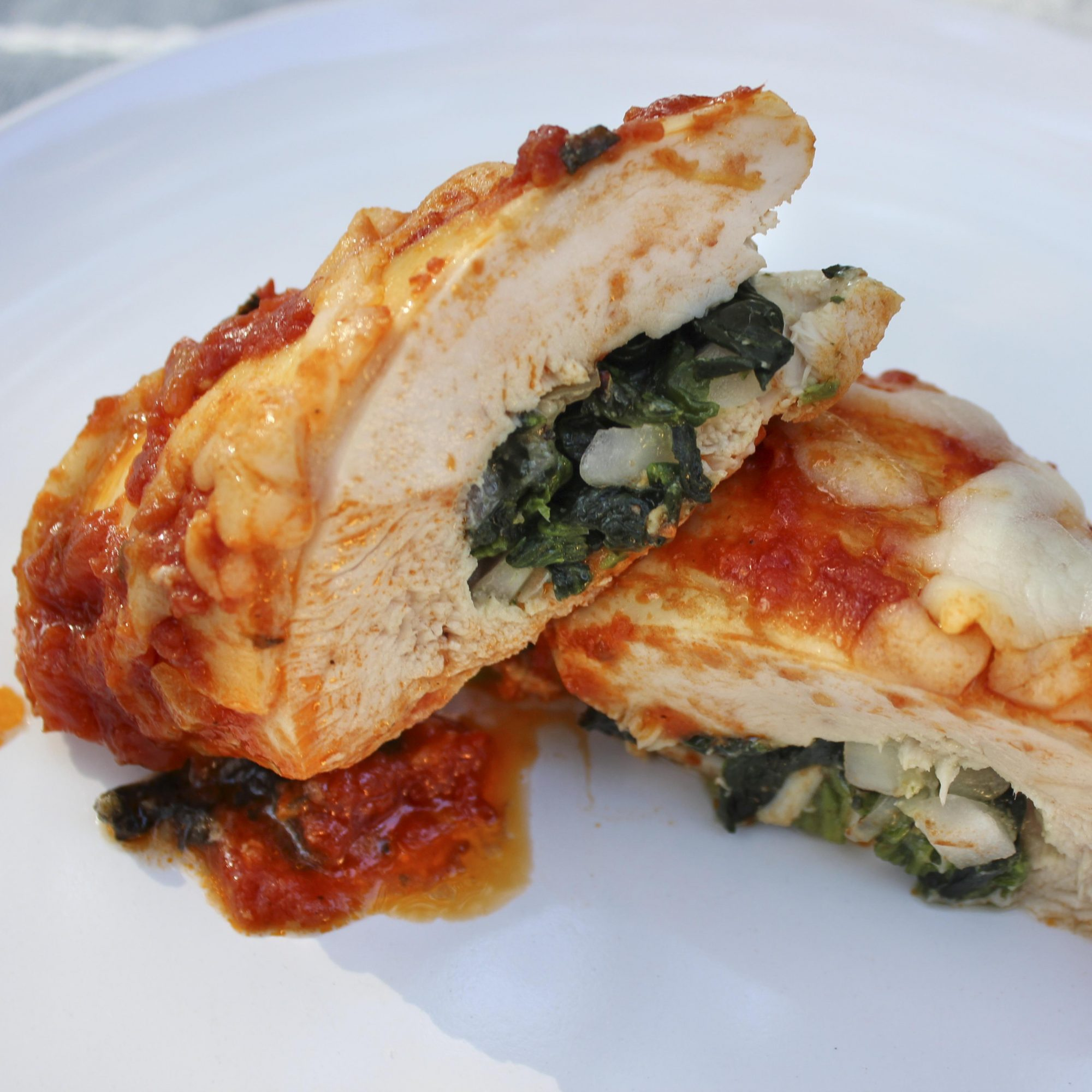Stuffed chicken breast cut in half to show spinach filling.