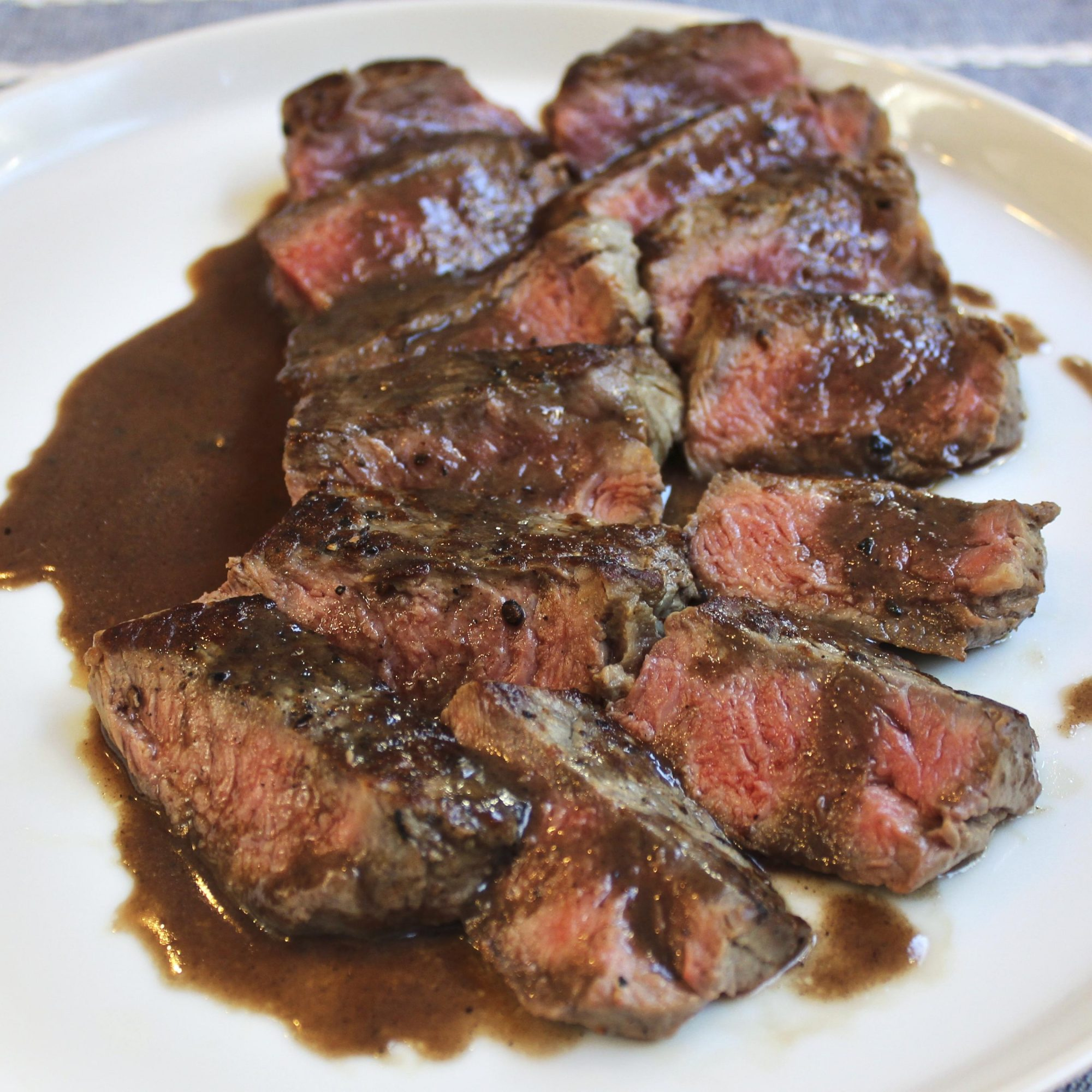 Bite sized pieces of medium rare New York Strips served on a low rimmed white plate and topped with a bordelaise pan sauce