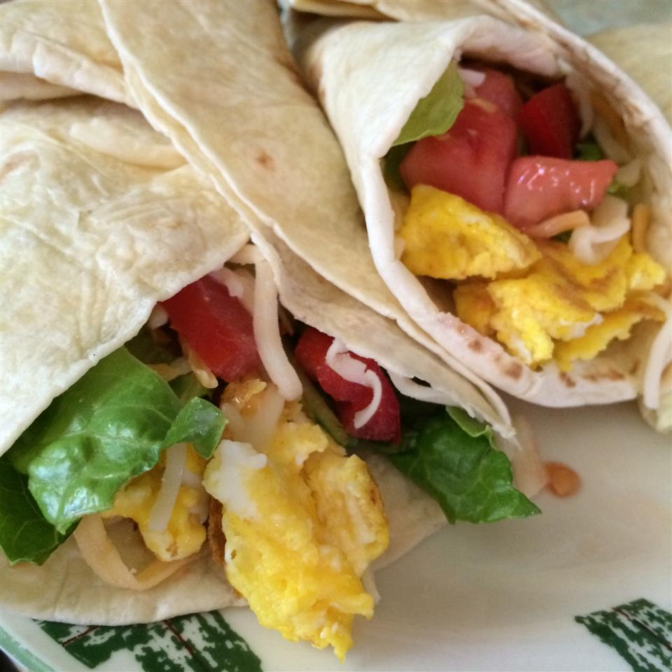 two breakfast tortillas with eggs, black beans, cheese, lettuce, and tomato