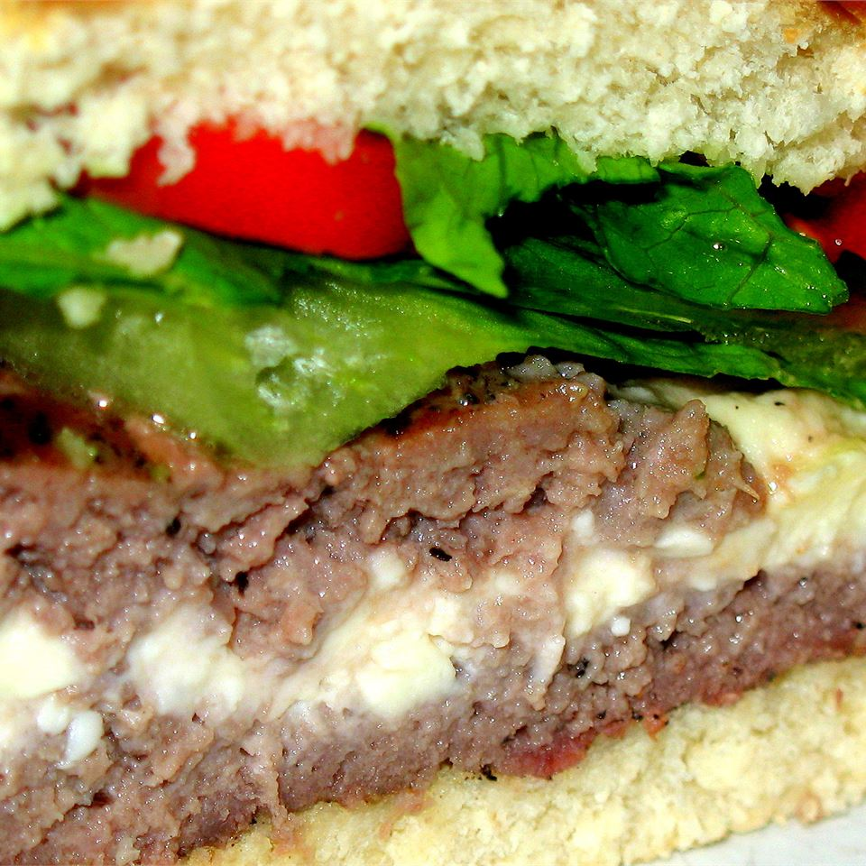 close up of hamburger stuffed with feta, topped with lettuce and tomato on bun