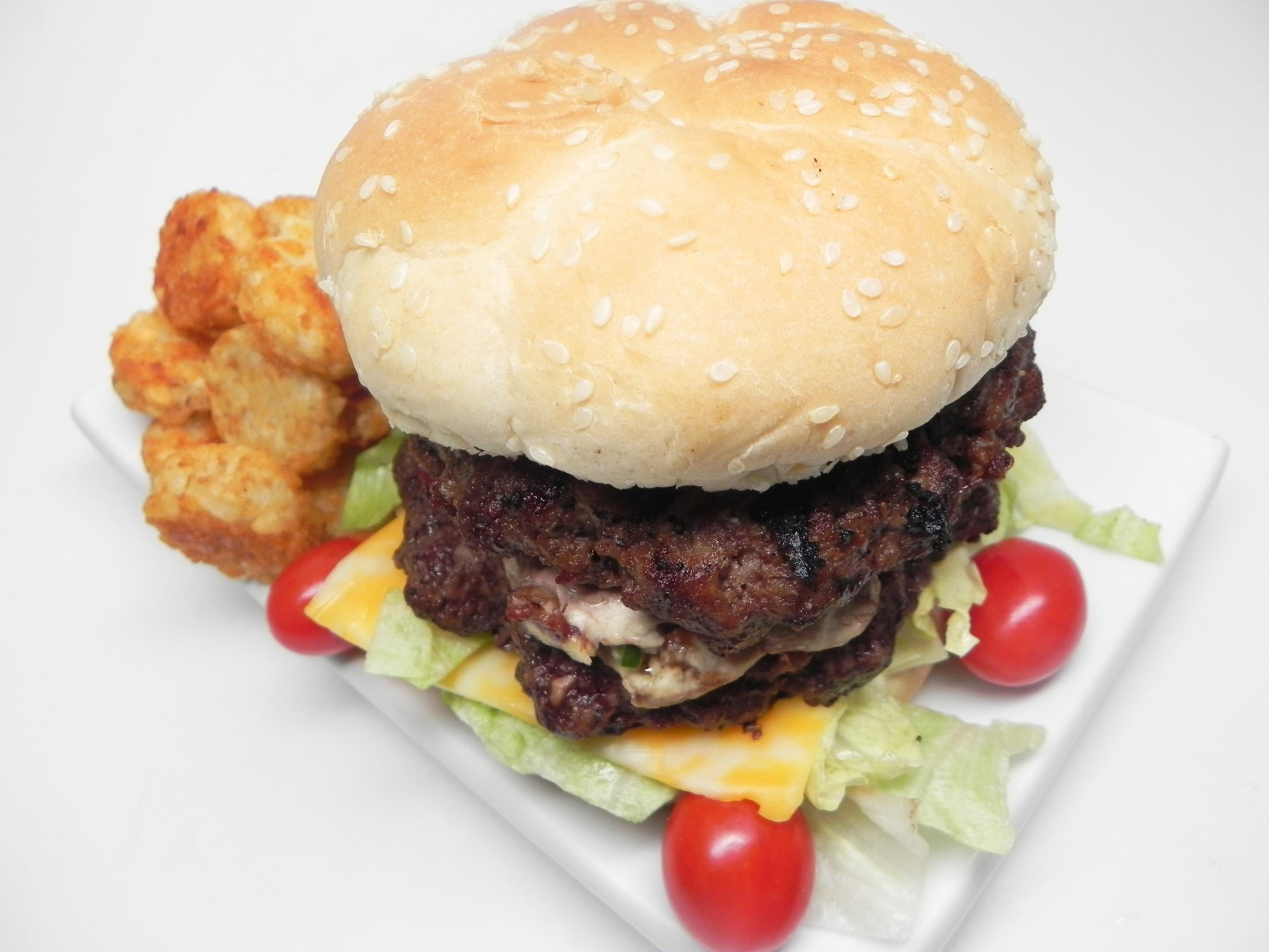 bacon and jalapeno cream cheese stuffed burger with cheese and lettuce