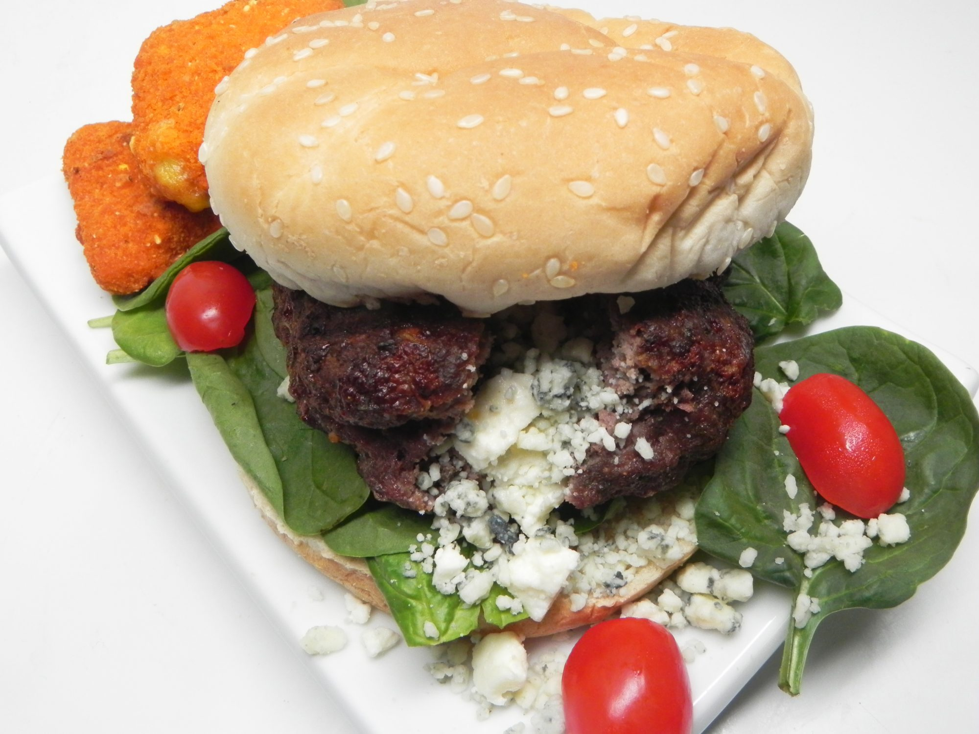 cheese stuffed burger on bun with spinach