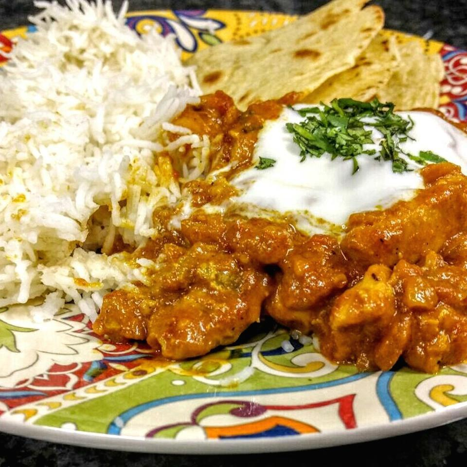 indian chicken curry with yogurt sauce, rice, and naan