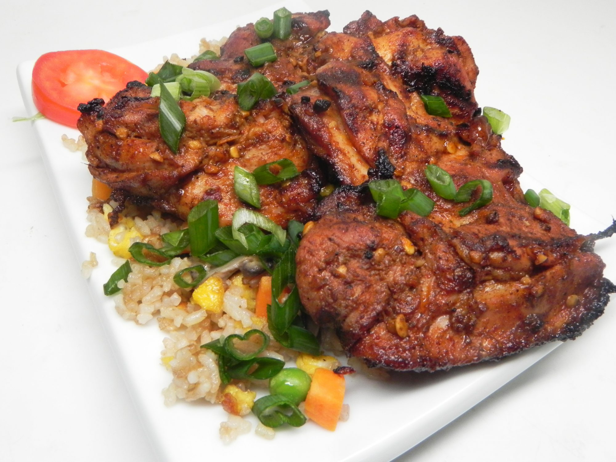 korean grilled chicken thighs over rice with green onions and vegetables