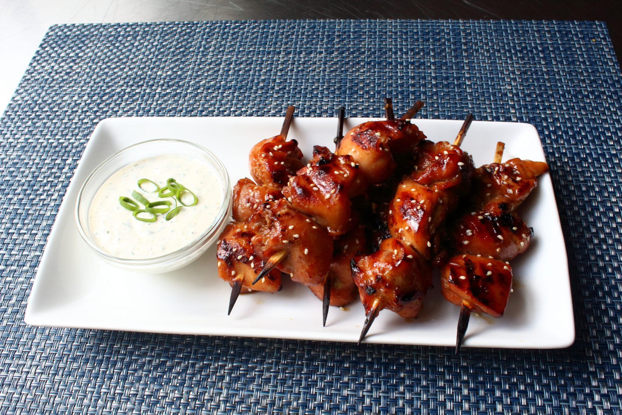 grilled chicken thighs on skewers with teriyaki sauce and white dipping sauce
