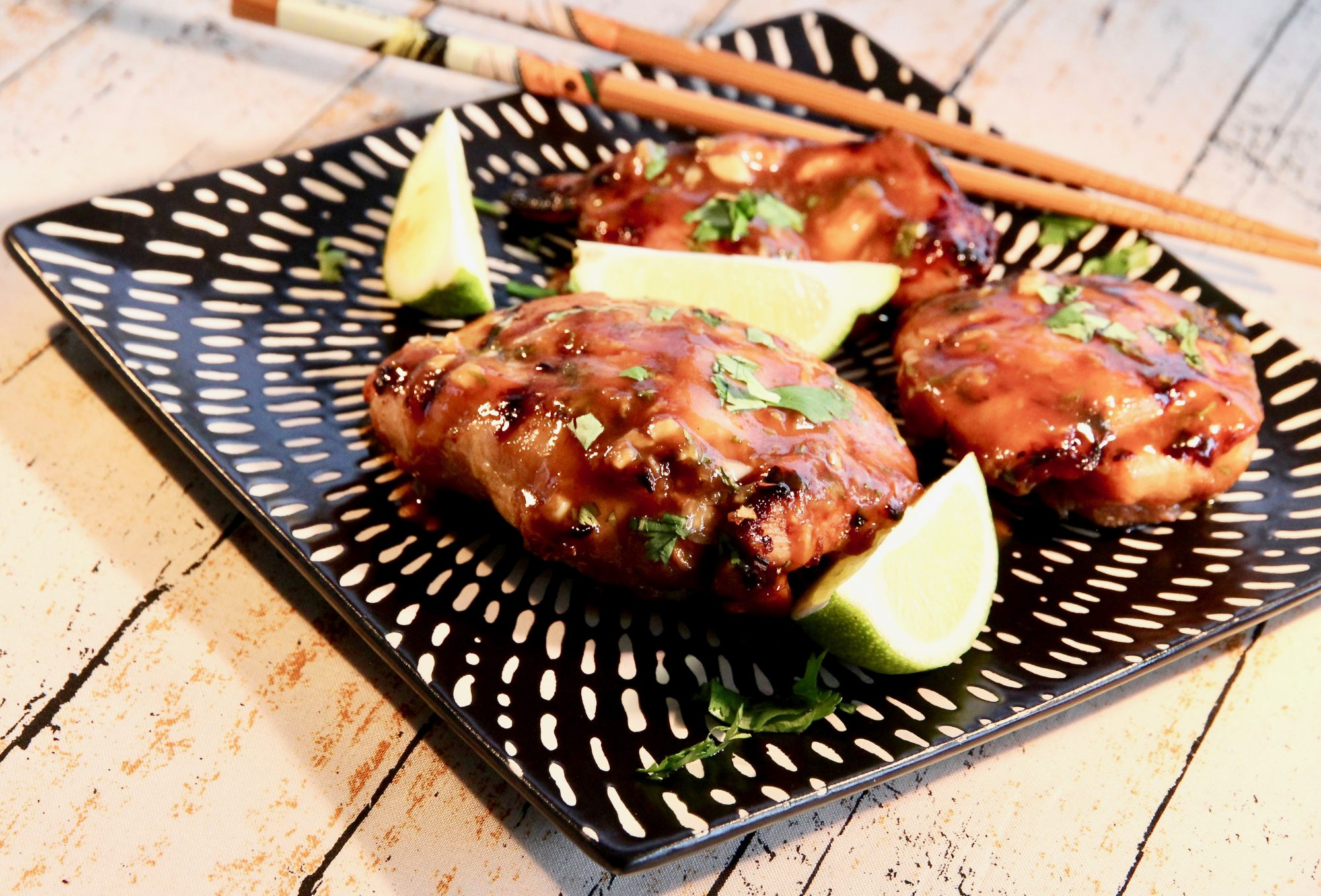 grilled chicken thighs with lime wedges on black patterned plate