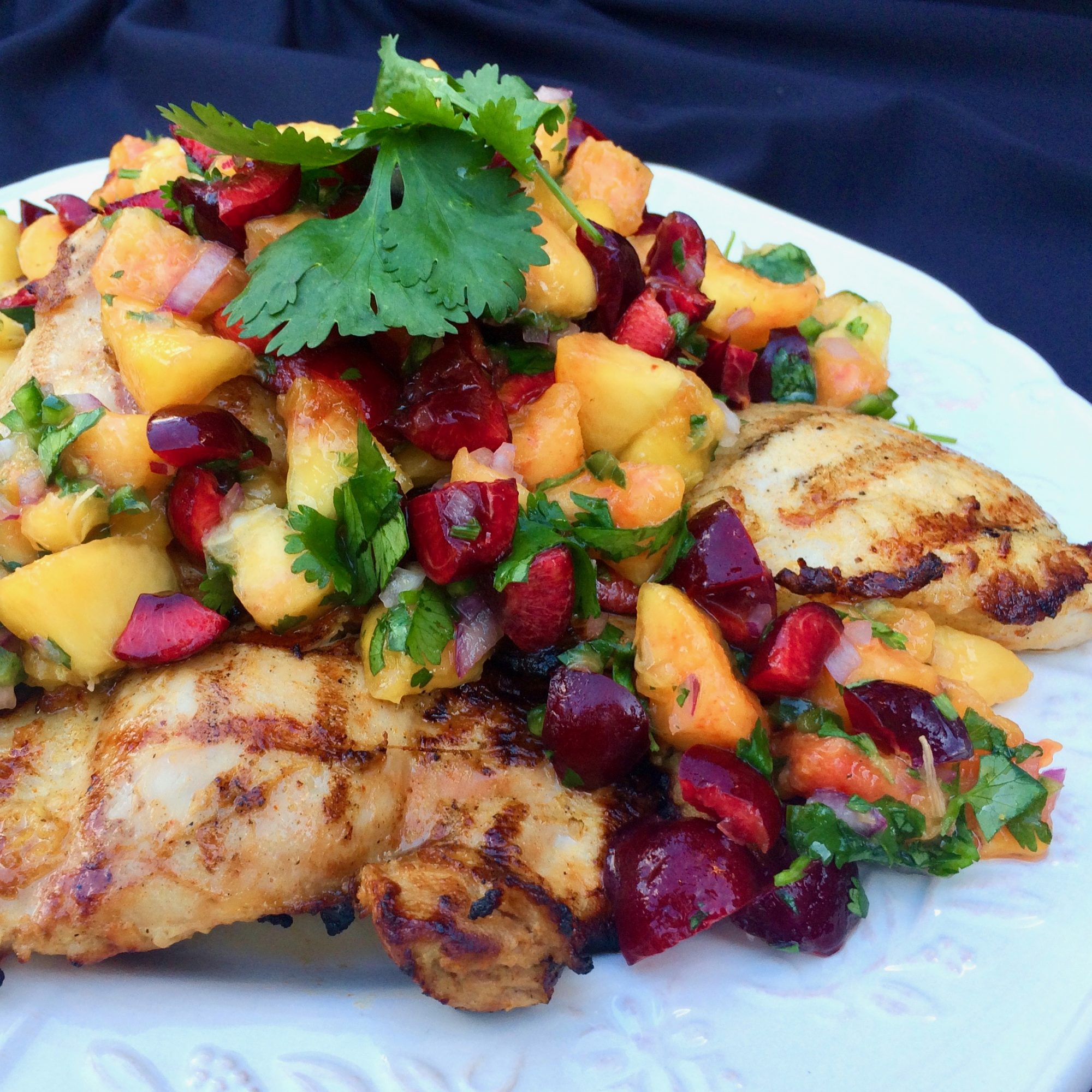 peach and cherry salsa on grilled chicken thighs