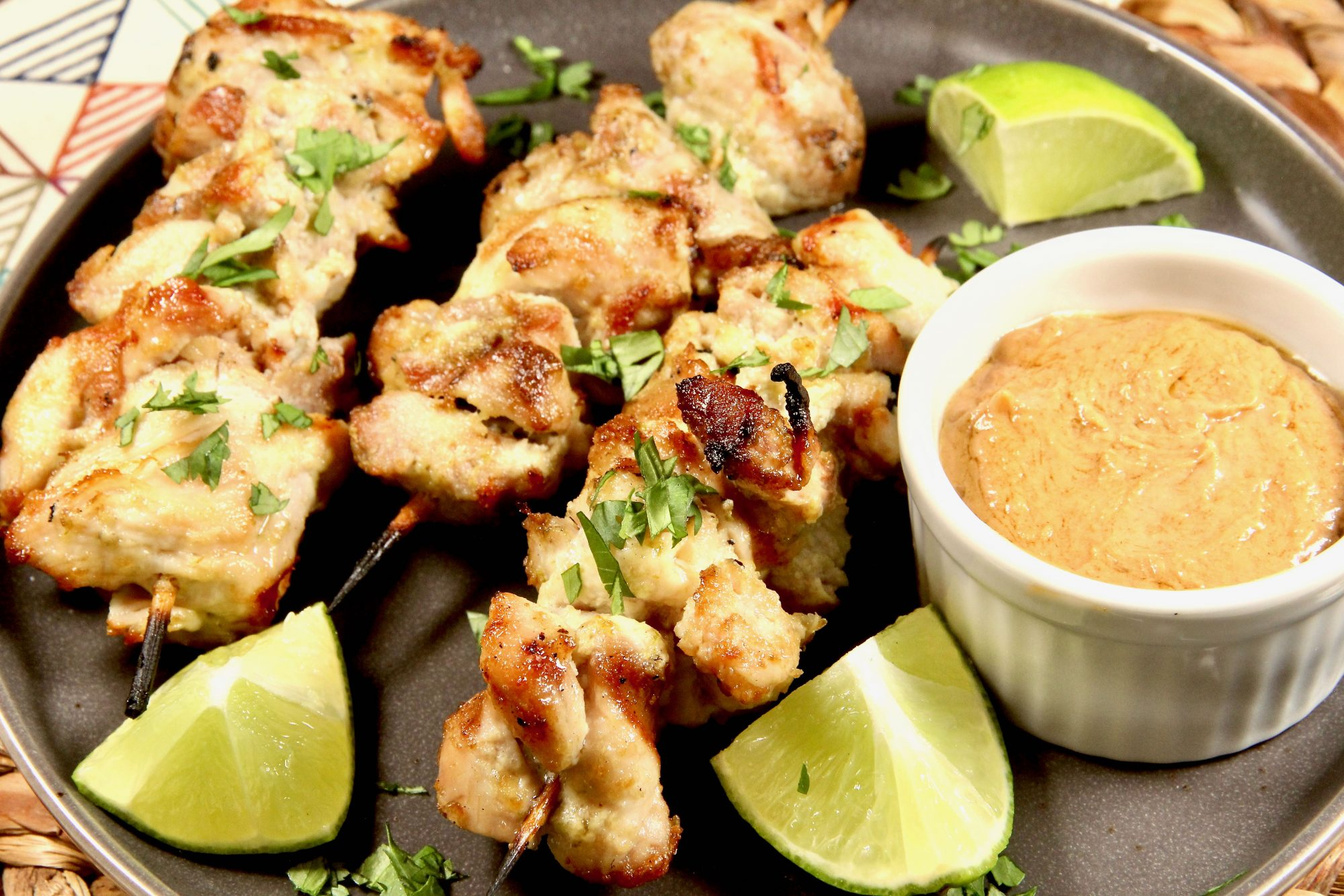 grilled chicken kabobs with lime wedges and peanut sauce