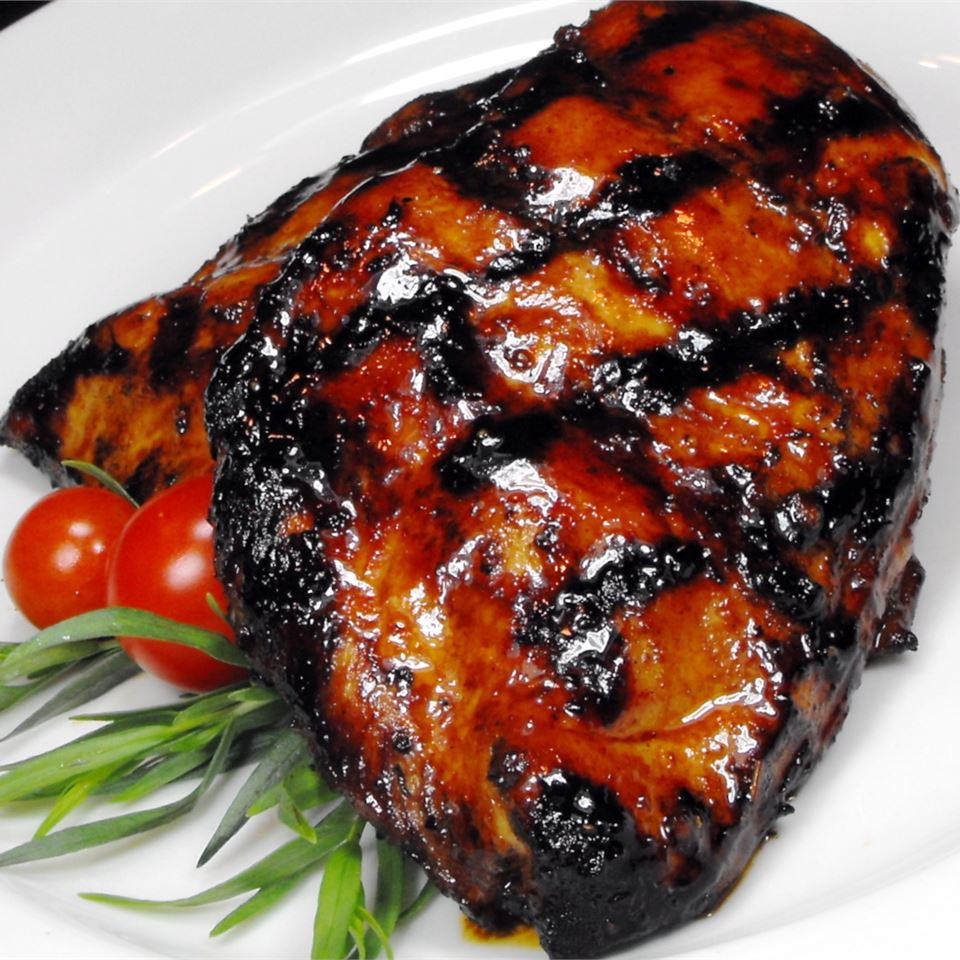 grilled chicken thigh with marinade, herbs, and cherry tomatoes