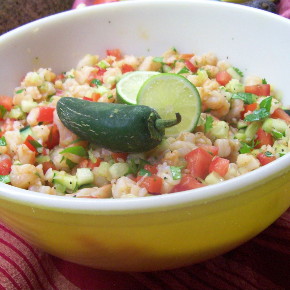 a yellow bowl of ceviche with lime and a chili pepper