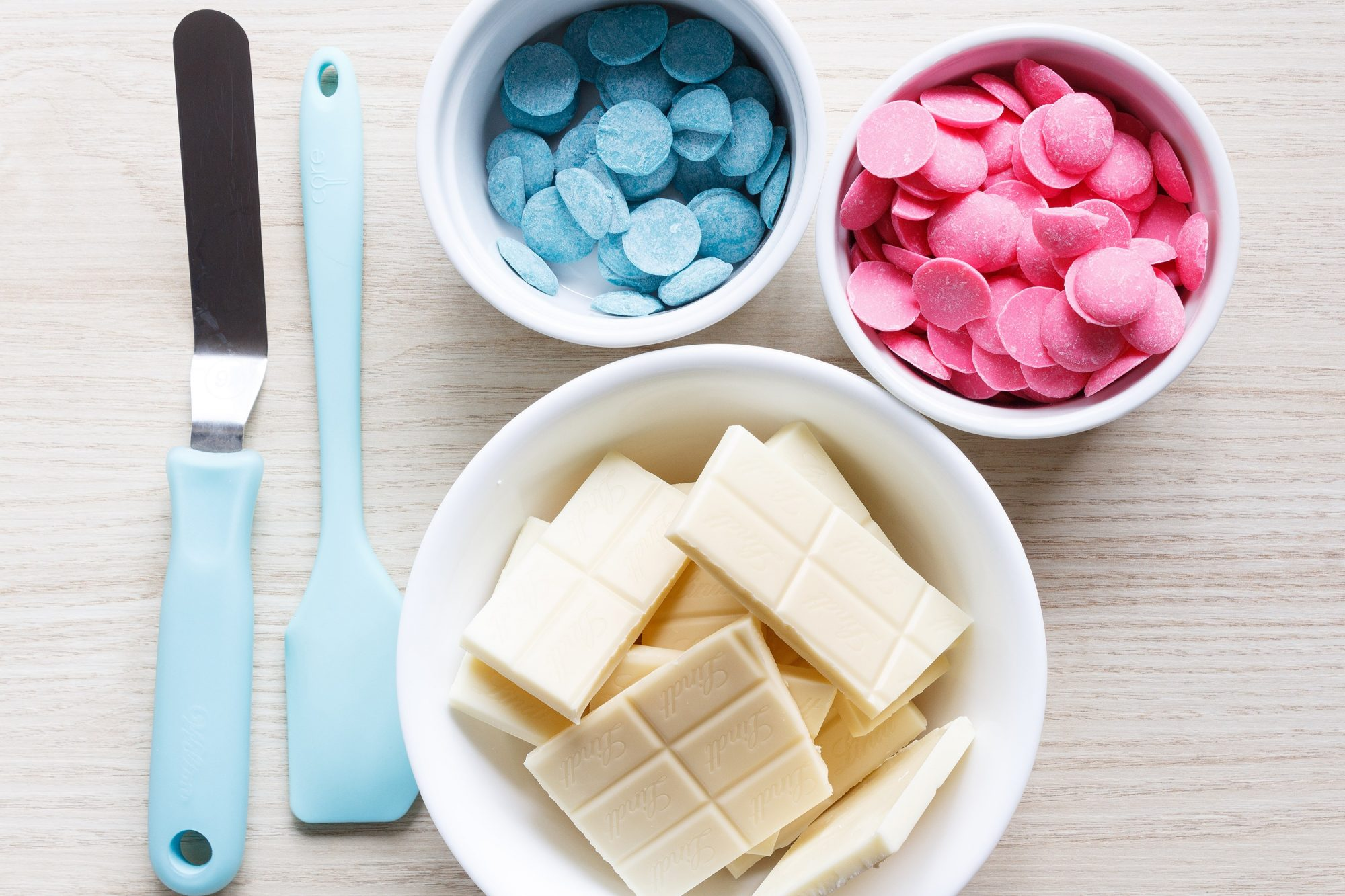 ingredients and tools to make unicorn bark: white chocolate, blue and pink candy wafers, bowls, spatulas