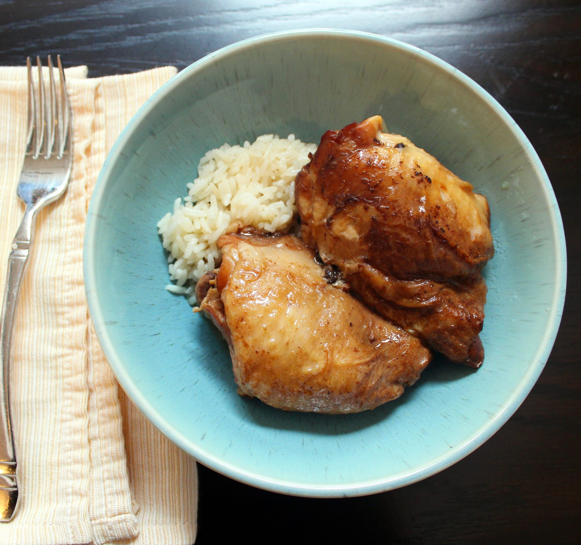 glazed chicken thighs over rice in blue bowl
