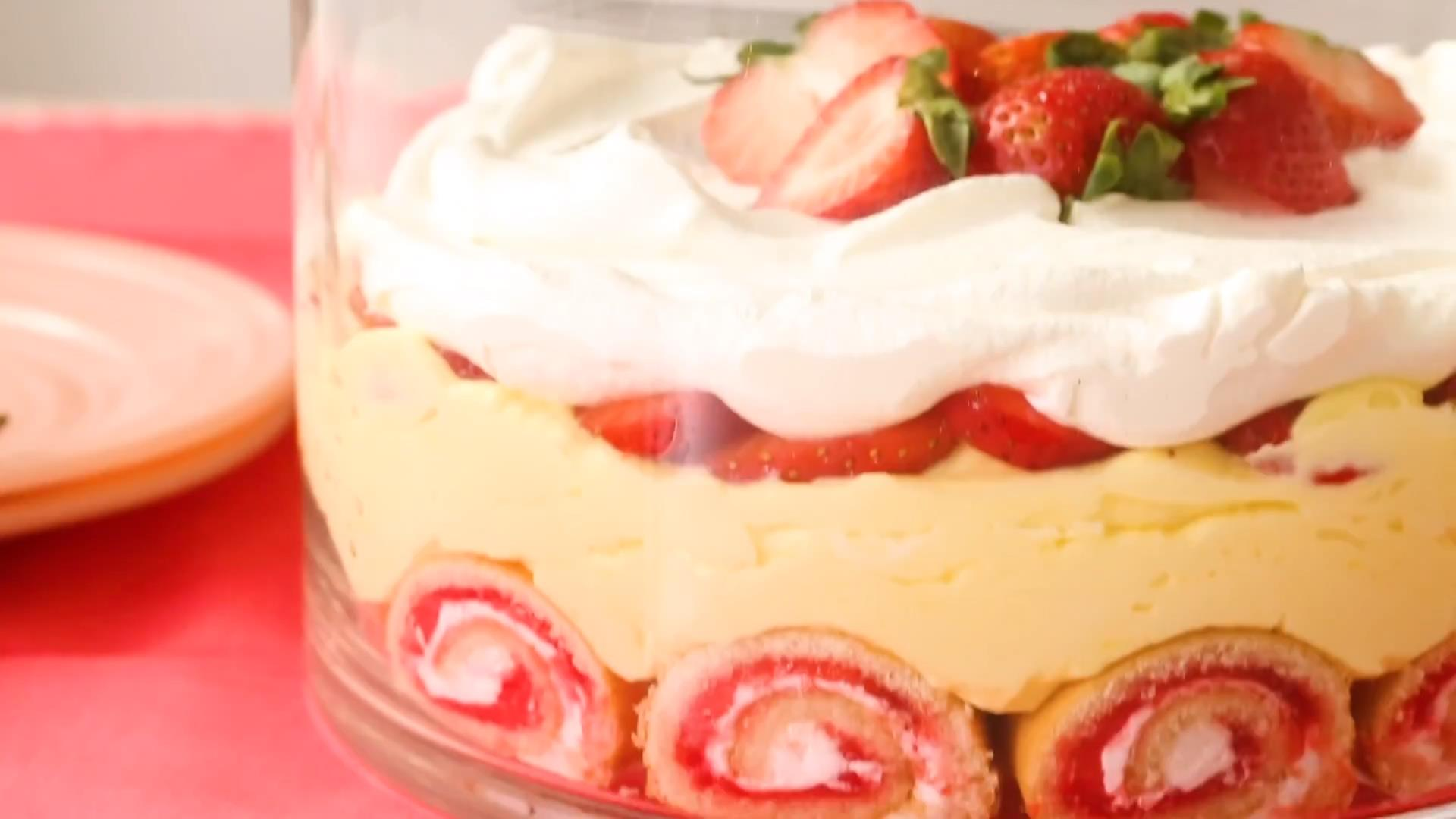 closeup of a glass bowl filled with layers of jelly roll, vanilla pudding, strawberries, and whipped topping