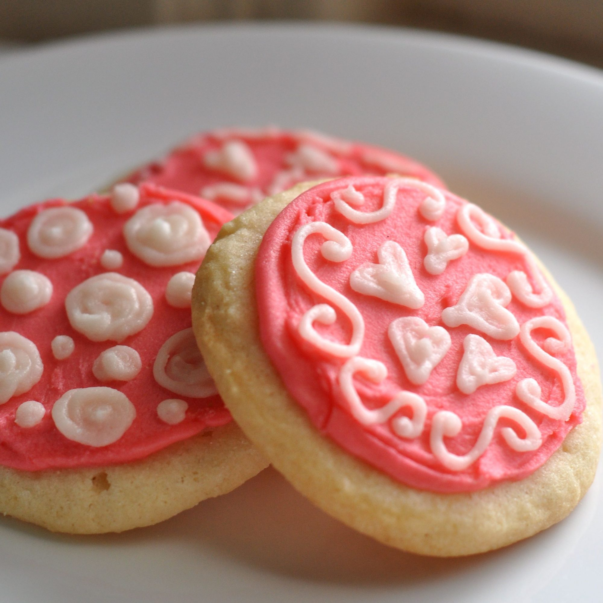 round cookies decorated for Valentine's Day with pink frosting and piped white frosting hearts and swirls