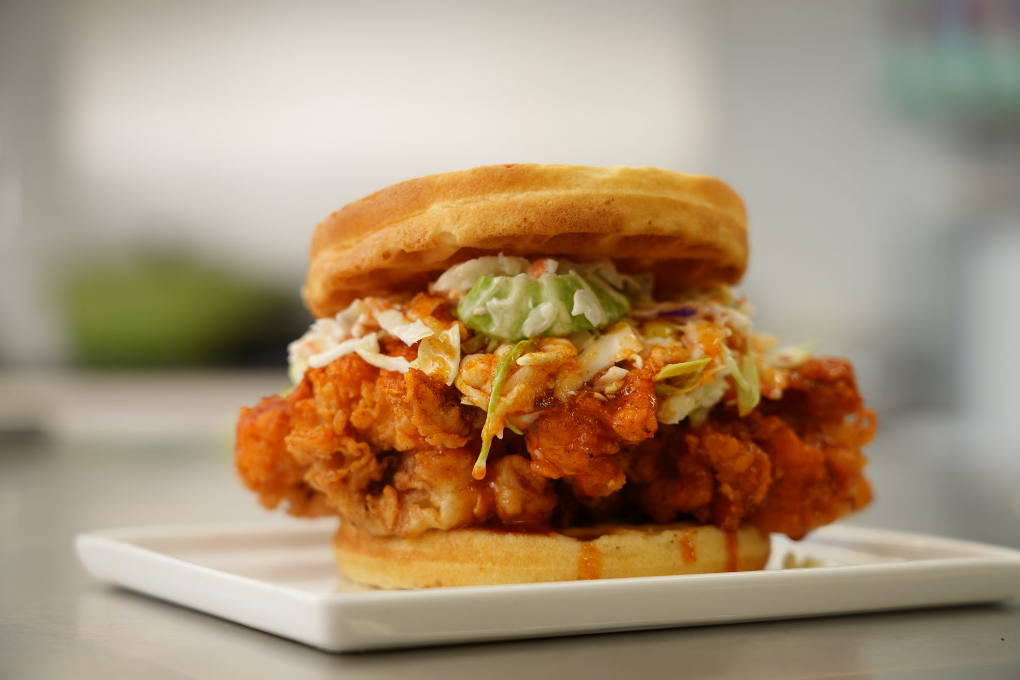 fried chicken and waffle sandwich topped with coleslaw