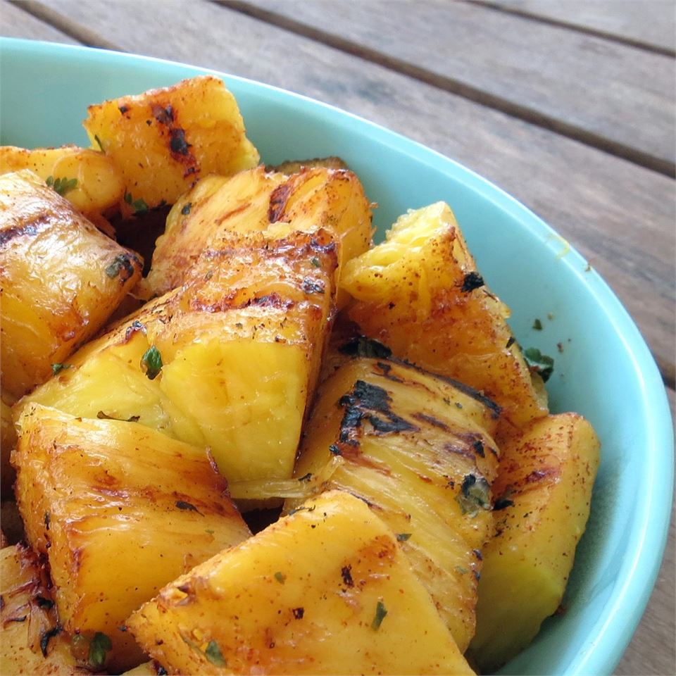 grilled pineapple chunks with seasoning in blue bowl