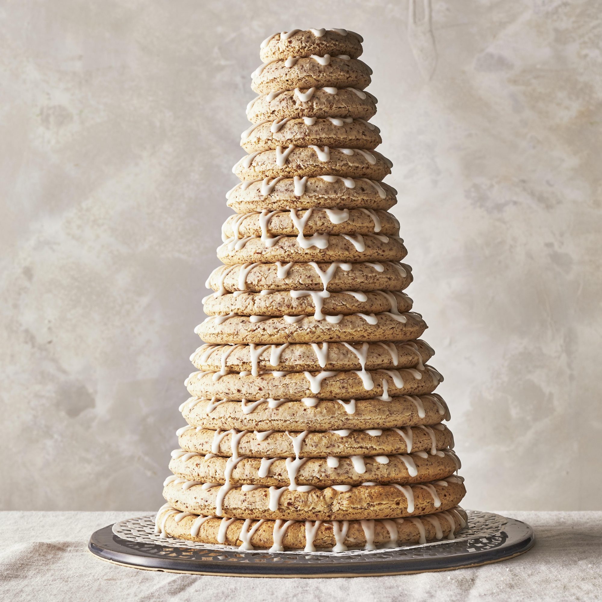 18 beautiful almond cookies, each drizzled with icing, and stacked to build a beautiful, towering, Kransekake (Norwegian Almond Ring Cake)