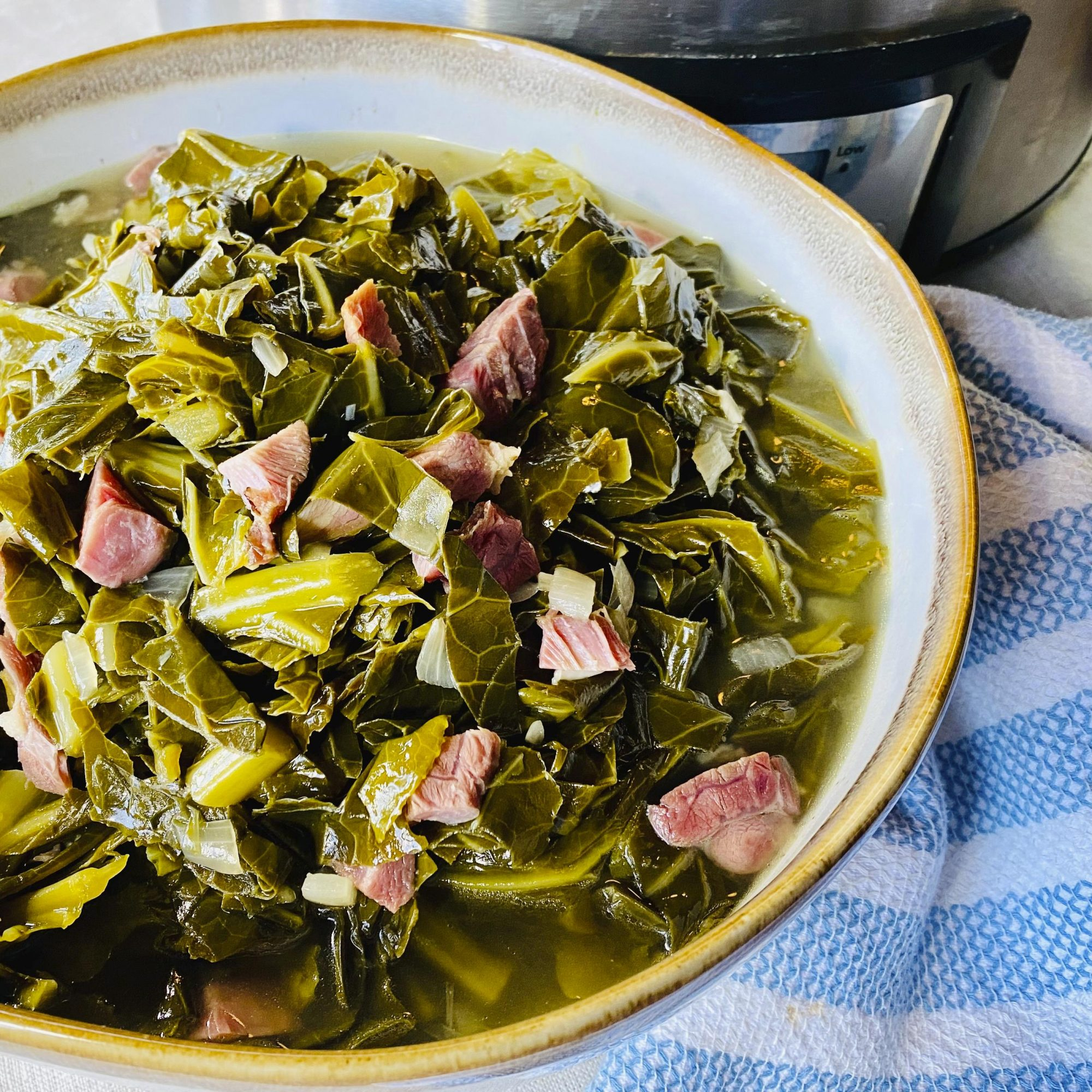 A bowl full of Slow Cooker Collard Greens sitting on top of a blue and white striped linen in front of the Slow Cooker.
