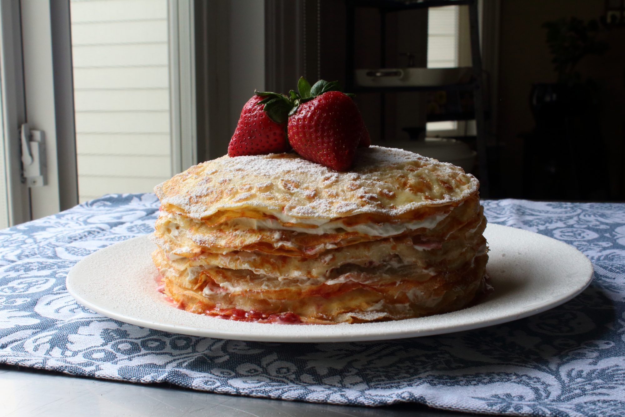 stacked crepes with whole strawberries and powdered sugar on plate