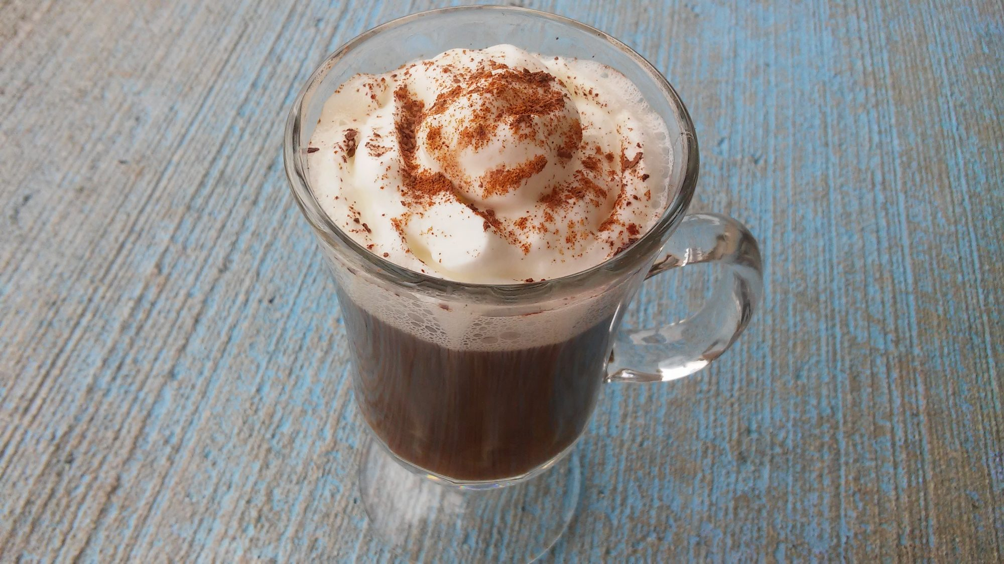 mexican tequila drink with whipped cream and cinnamon in glass