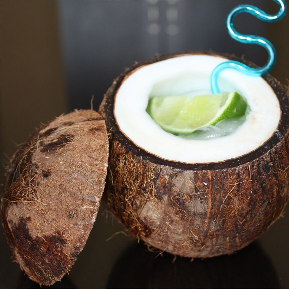 coconut with tequila cocktail inside and lime wedge