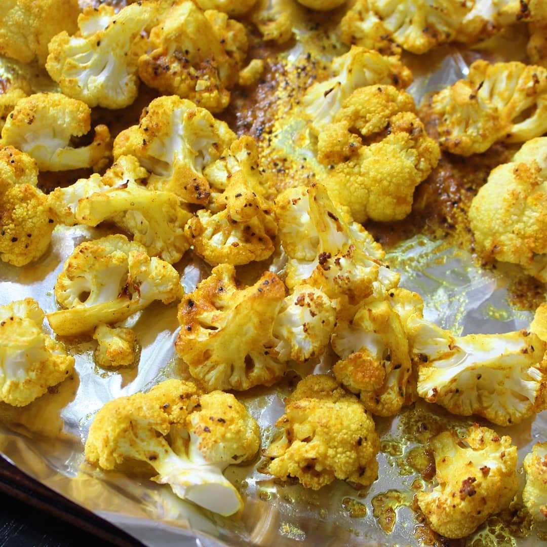 tight shot yellow roasted cauliflower on foiled sheet pan