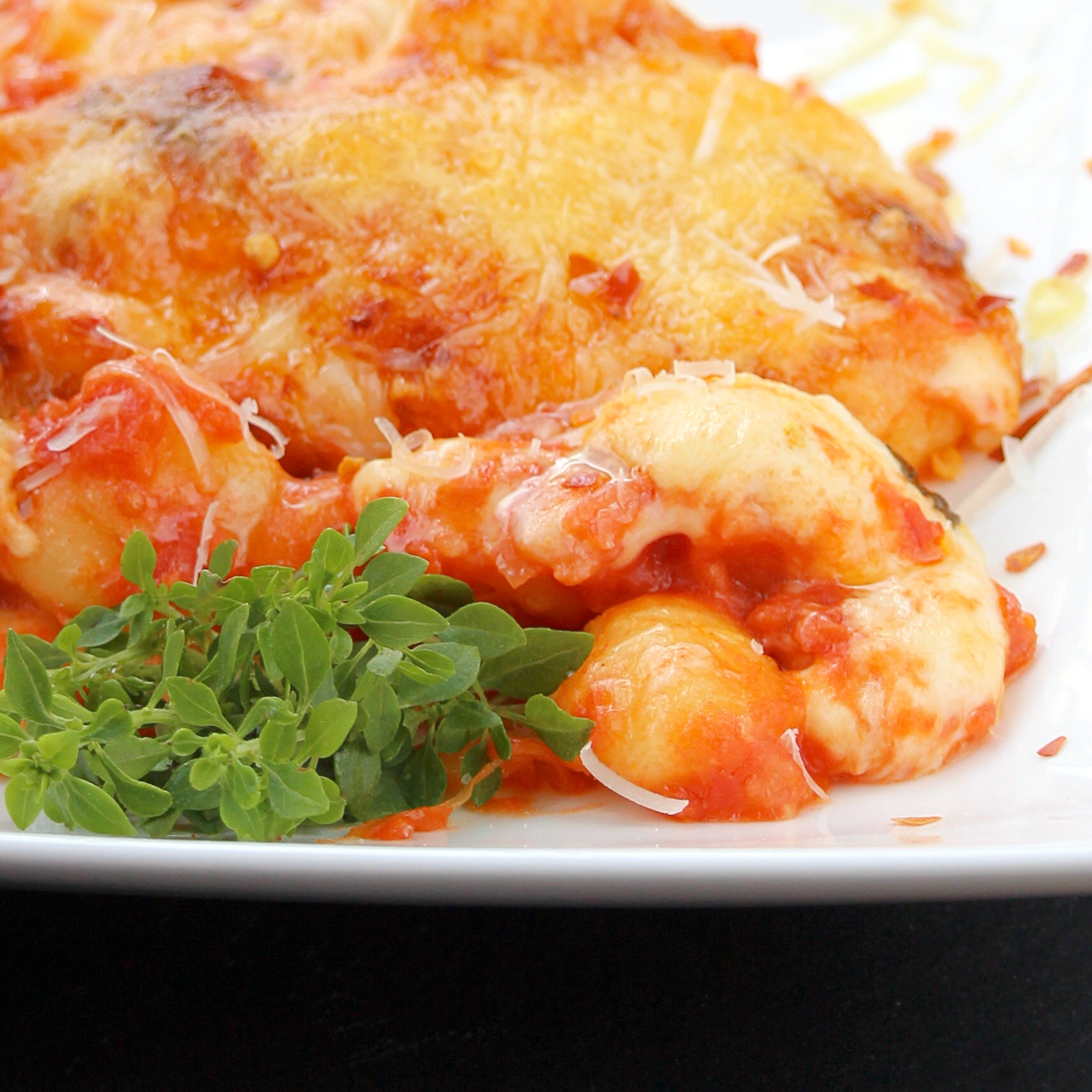 potato gnocchi with tomato sauce and cheese on a white plate