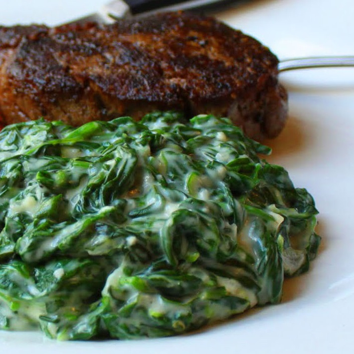 close up of Fast and Easy Creamed Spinach and steak on a plate
